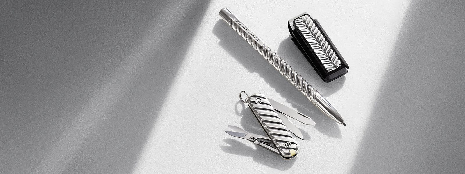 Modern Cable Swiss Army knife in sterling silver, Cable pen in silver and gold-plated brass and Chevron money clip in sterling silver and black aluminum, in a ray of light on a textured white stone.