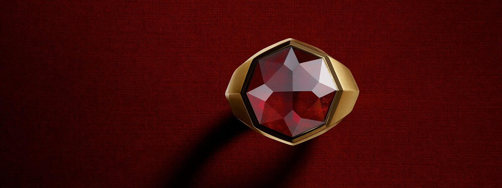 An aerial image of a men's DY Fortune faceted signet ring in 18K yellow gold with garnet, standing upright on a textured red surface.