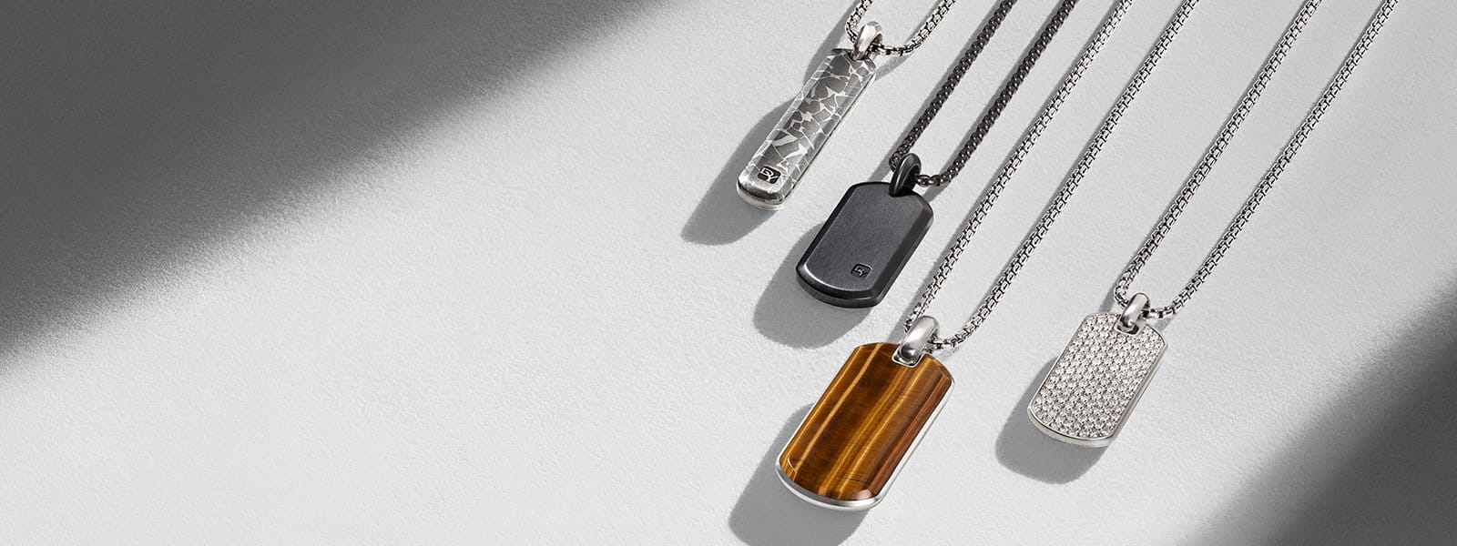 Meteorite, Streamline and Exotic Stone tags in sterling silver or black titanium with fused meteorite, tiger's eye or white diamonds, strung on chains and arranged in a diagonal row in a ray of light on a textured white stone.