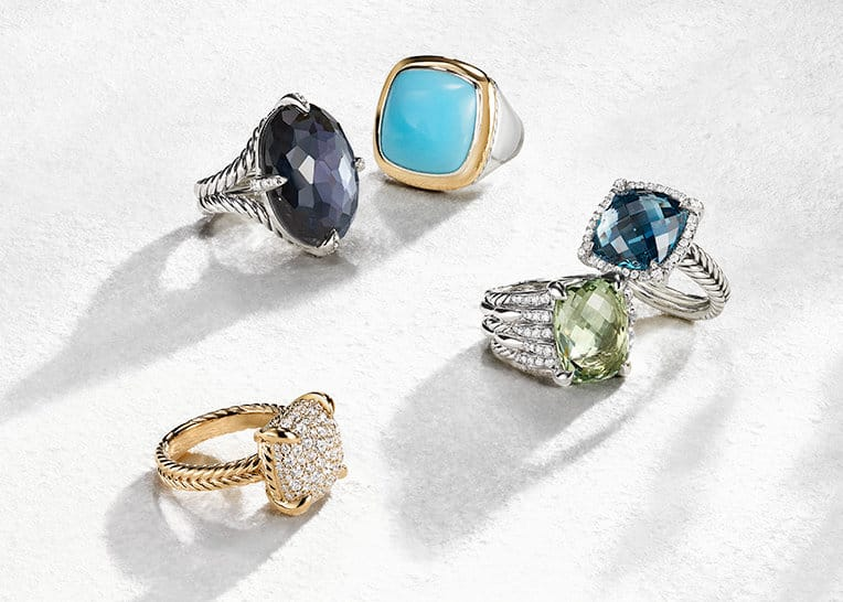 David Yurman Châtelaine® and Albion® rings in 18K rose gold, sterling silver or sterling silver with 18K yellow gold, colored gemstones and pavé diamonds shot against a white stone with long shadows.