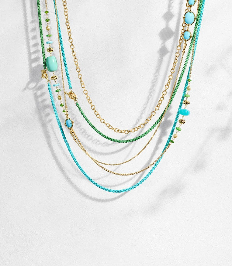 DY Bel Aire necklaces in turquoise or green stainless steel with 18K yellow gold and Bijoux, Chatelaine and Chain necklaces in 18K yellow gold with or without amazonite, turquoise and green diopside, hanging as bib layers with long shadows in front of a white stone background.