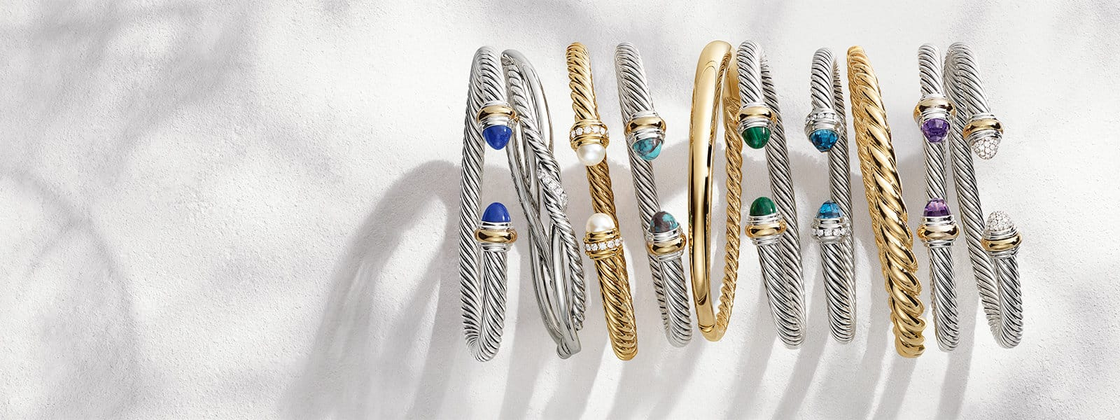 A horizontal stack of David Yurman The Cable Collection®, Continuance® and Pure Form® bracelets in sterling silver with or without diamonds, 18K yellow gold or colored gemstones on a white textured stone with long shadows.