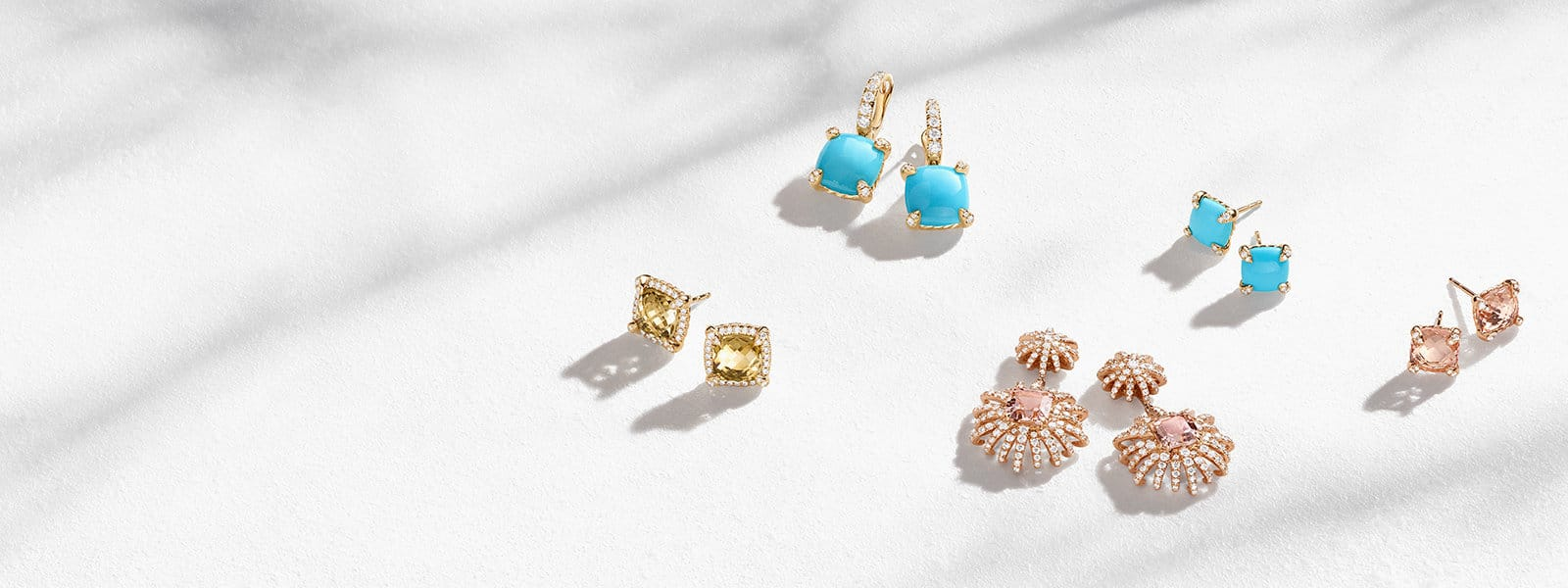 David Yurman Châtelaine® and Starburst earrings in 18K yellow or rose gold with citrine, turquoise or morganite and diamonds scattered on a white textured stone with long shadows.