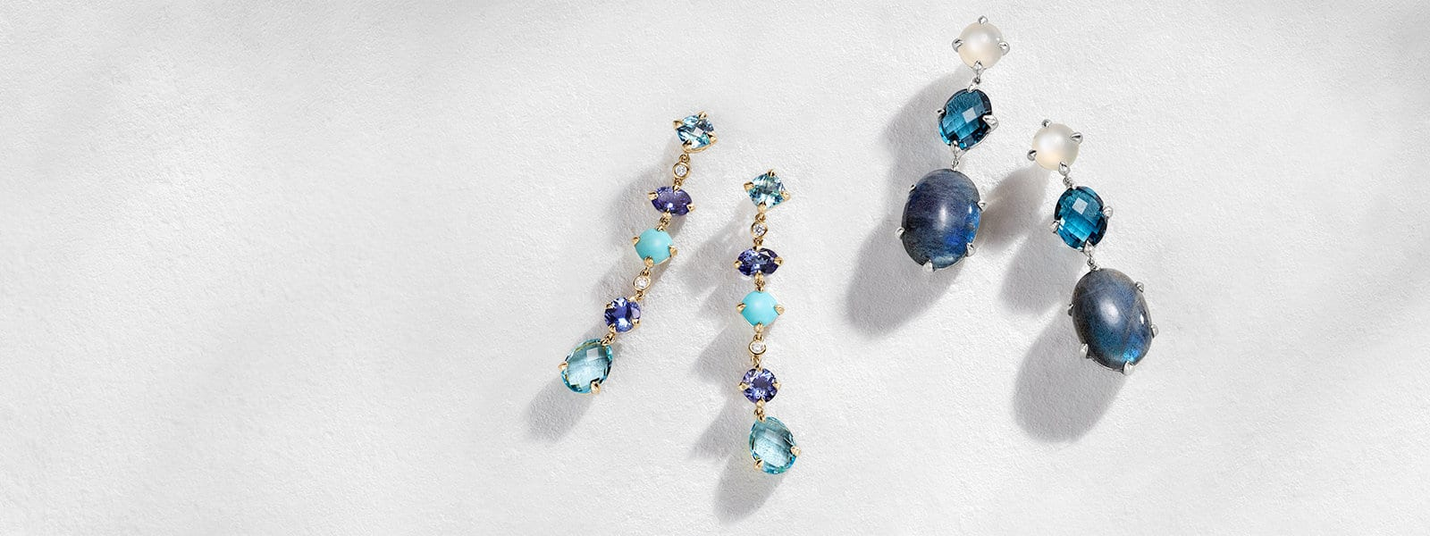 David Yurman Châtelaine drop earrings in 18K yellow gold with blue topaz, tanzanite, turquoise and diamonds or in sterling silver with labradorite, Hampton blue topaz and white moonstone on a white textured stone with long shadows.