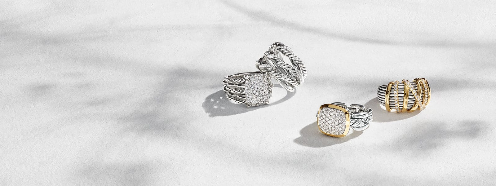 David Yurman Tides, Continuance®, and Helena rings in sterling silver with diamonds or diamonds and 18K yellow gold scattered on a white textured stone with long shadows.