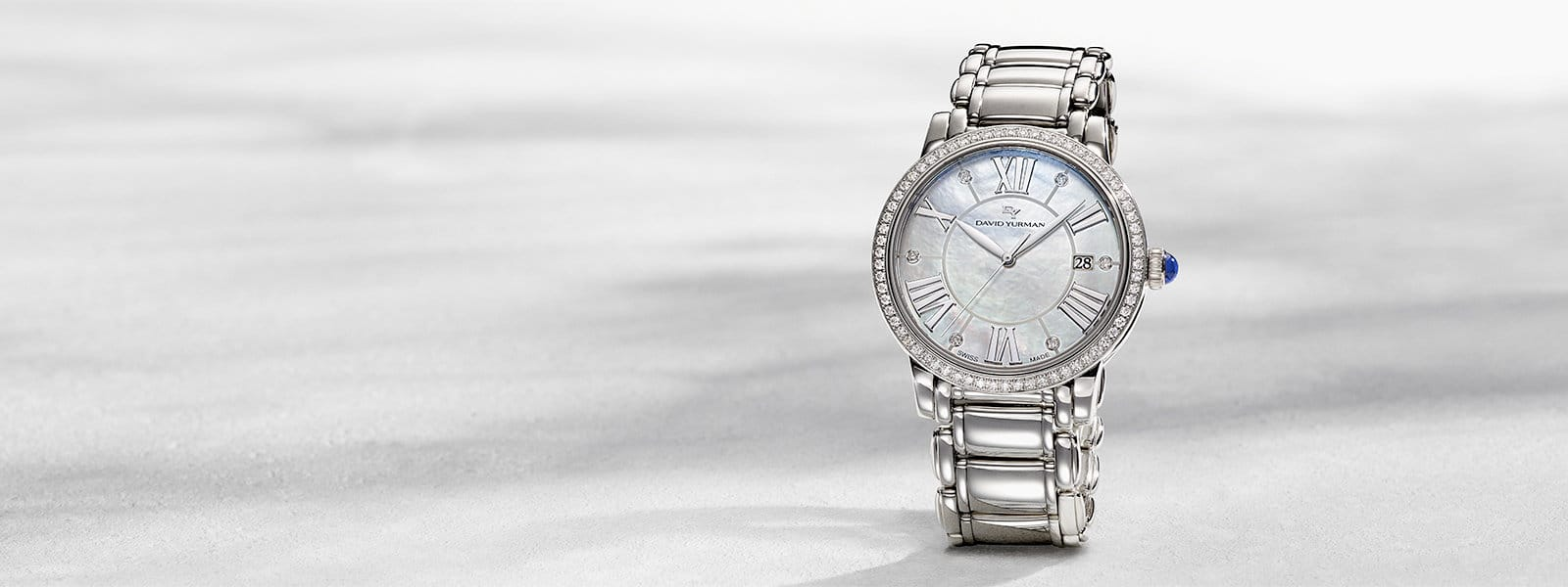 A David Yurman Classic quartz watch in stainless steel with a mother-of-pearl dial and diamonds standing upright on a white textured stone with long shadows.