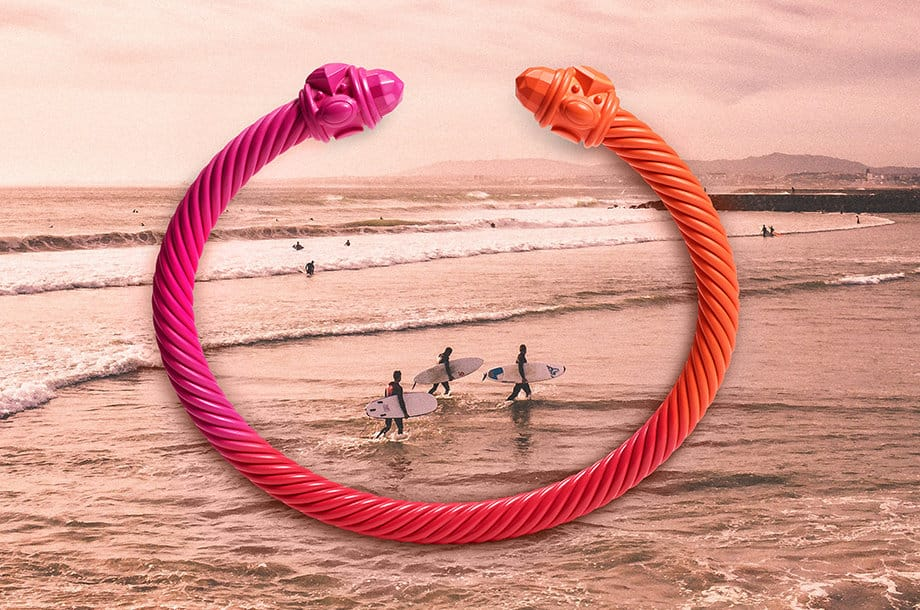 A David Yurman aluminum Renaissance Cable bracelet in a pink-orange ombré atop a photo of surfers.