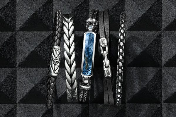 A color photograph shows a row of David Yurman men's bracelets from the Chevron, Exotic Stone, Streamline and Chain collections. One bracelet is crafted from sterling silver with woven black rubber or woven smooth black leather. One bracelet is crafted from sterling silver. Two bracelets are crafted from woven smooth black leather and sterling silver with or without pietersite. One bracelet is crafted from sterling silver with woven black nylon.