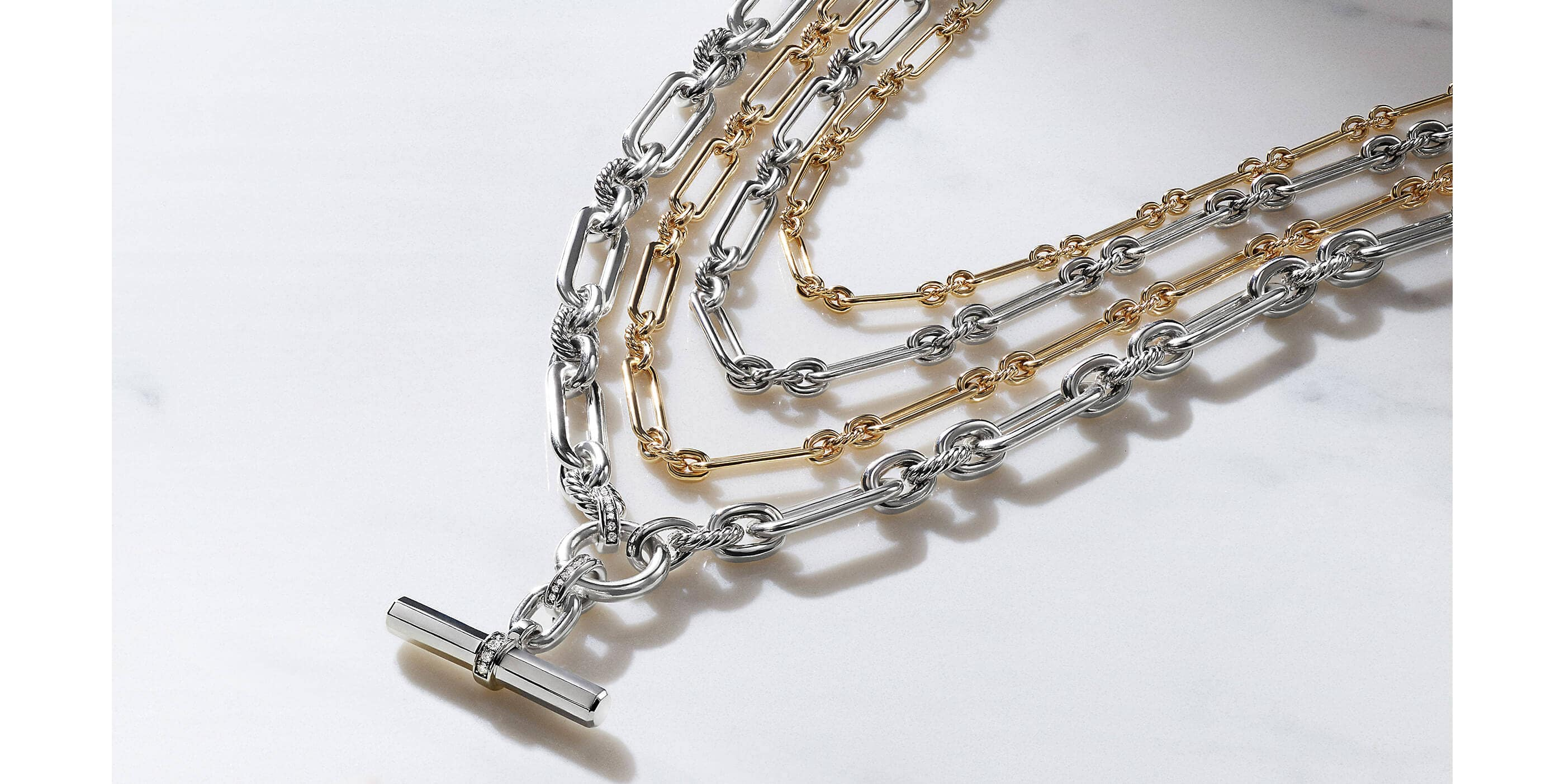 A color photo shows four David Yurman women's Lexington chain necklaces placed in a row on a marble surface in between a white-and-pink flower on the left and a perfume bottle atop black-and-white postcards on a white saucer on the right. The women's jewelry is crafted from 18K yellow gold or sterling silver with or without pavé diamond accents.
