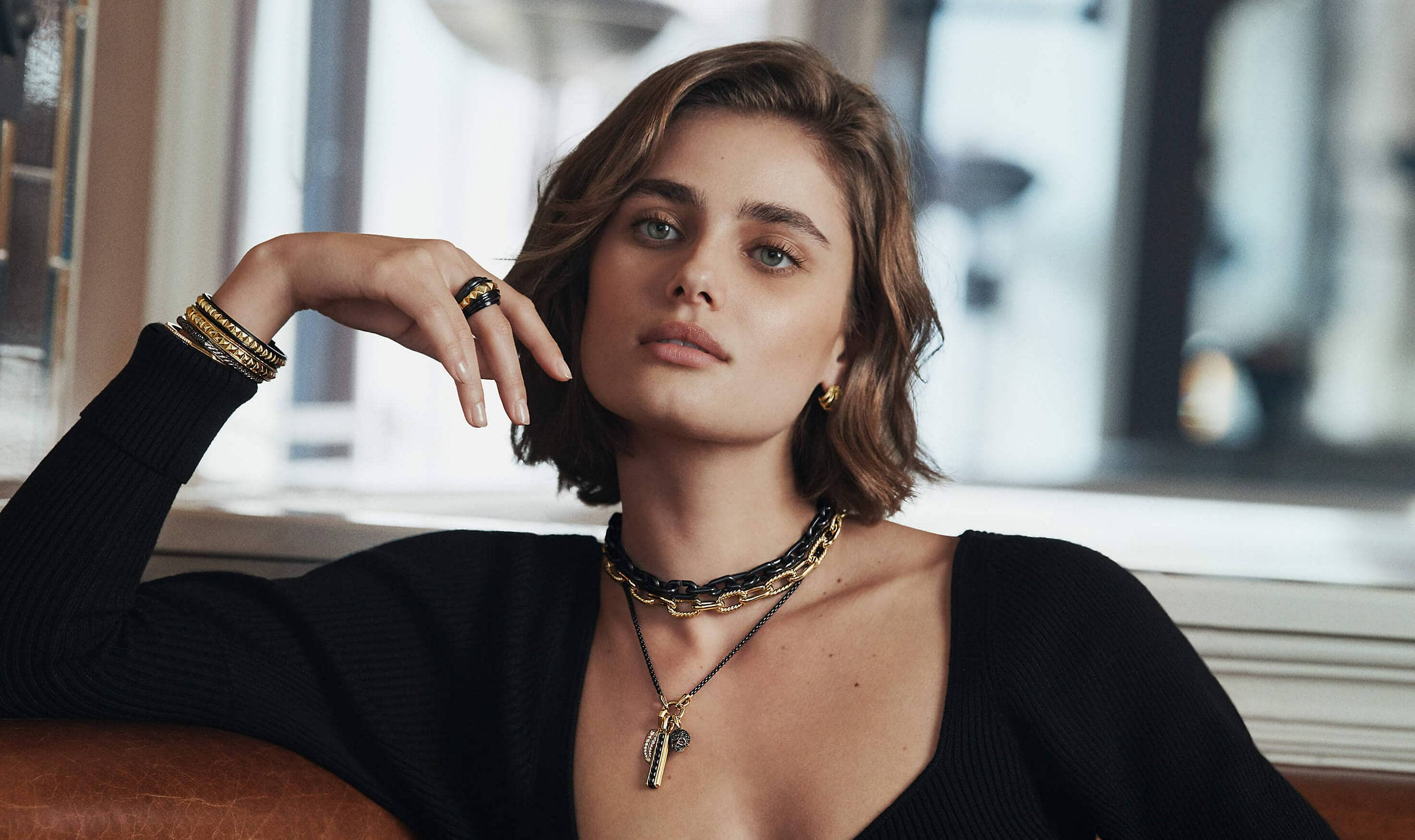 A color photo shows model Taylor Hill from the shoulders up dressed in a black top in front of a sunlit window. She's wearing a pair of David Yurman huggie hoop earrings, a ring, three chain necklaces including one strung with three amulets and a stack of bracelets on one hand. The jewelry is crafted from 18K yellow gold with or without black titanium or white or black diamonds.