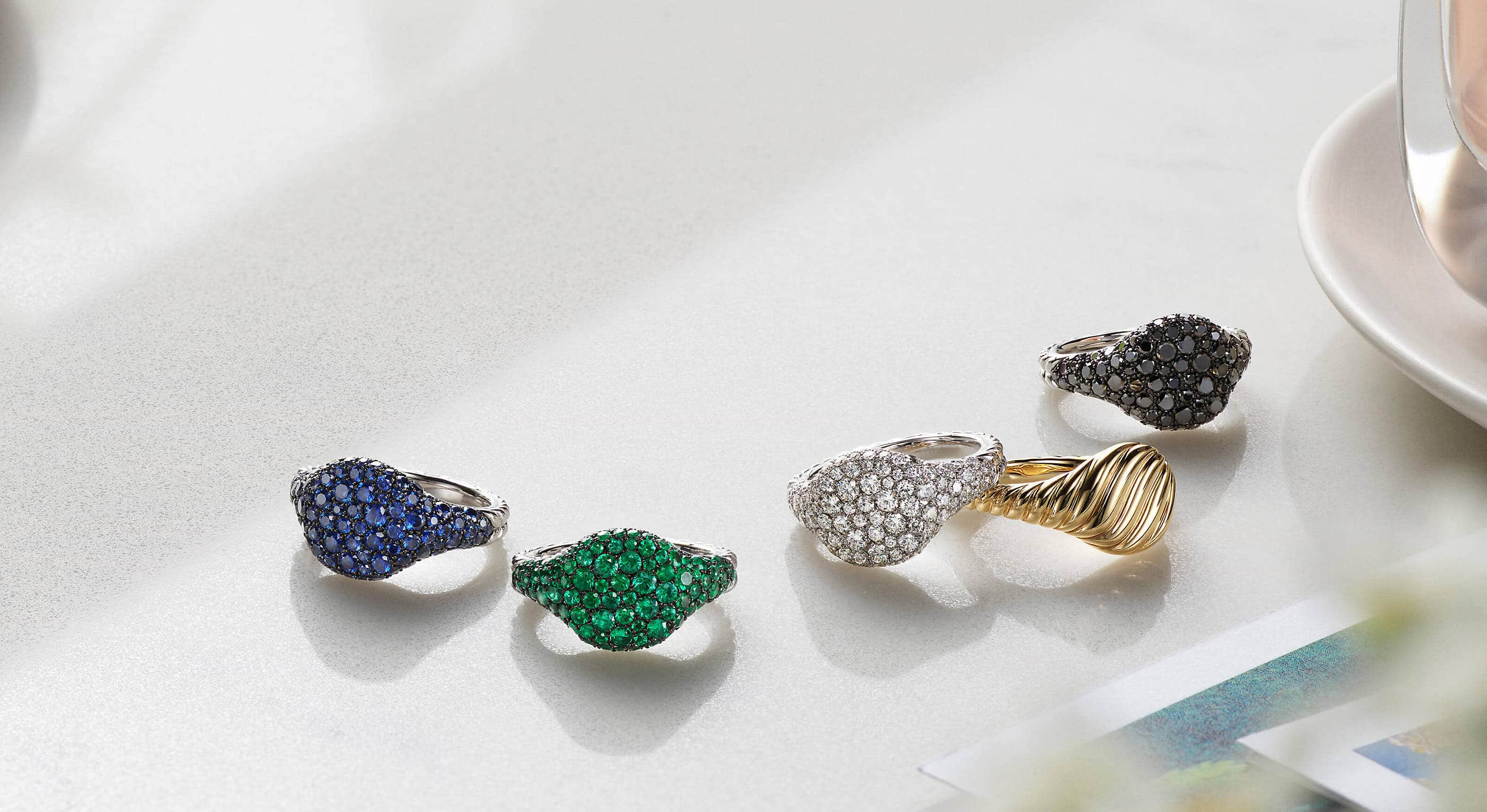 A color photo shows five David Yurman women's pinky rings scattered on a white surface next to a perfume bottle on a white saucer and color photographs. Four rings are crafted from 18K white gold encrusted with sapphires, emeralds or black or white diamonds. One ring is crafted from Cabled yellow gold.