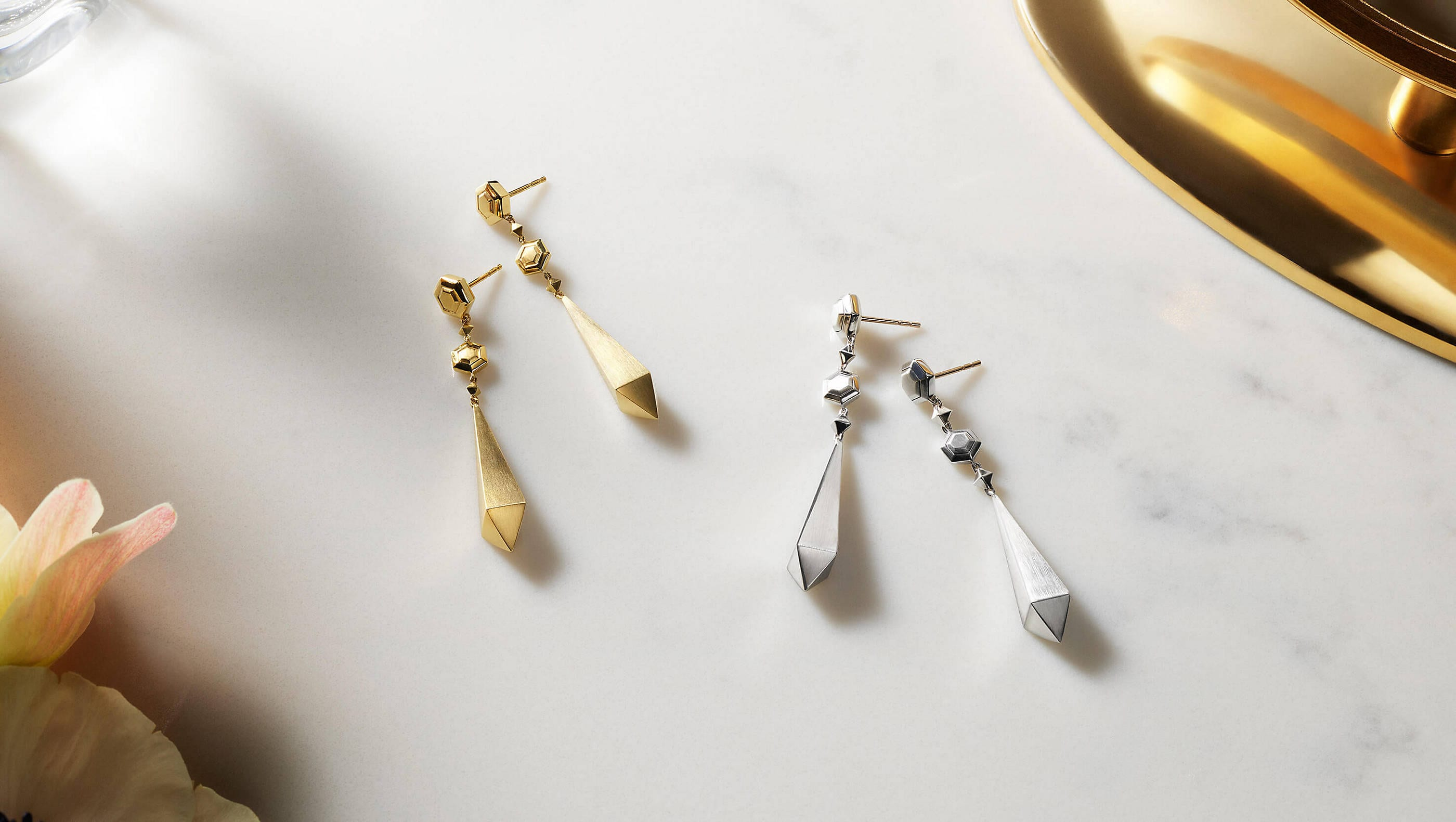 A color photo shows two pairs of David Yurman women's earrings from the Modern Renaissance collection scattered on a grey marble surface nearby a white-and-pink flower, a perfume bottle and a golden tray. One pair is crafted from 18K yellow gold and the other pair is crafted from sterling silver.
