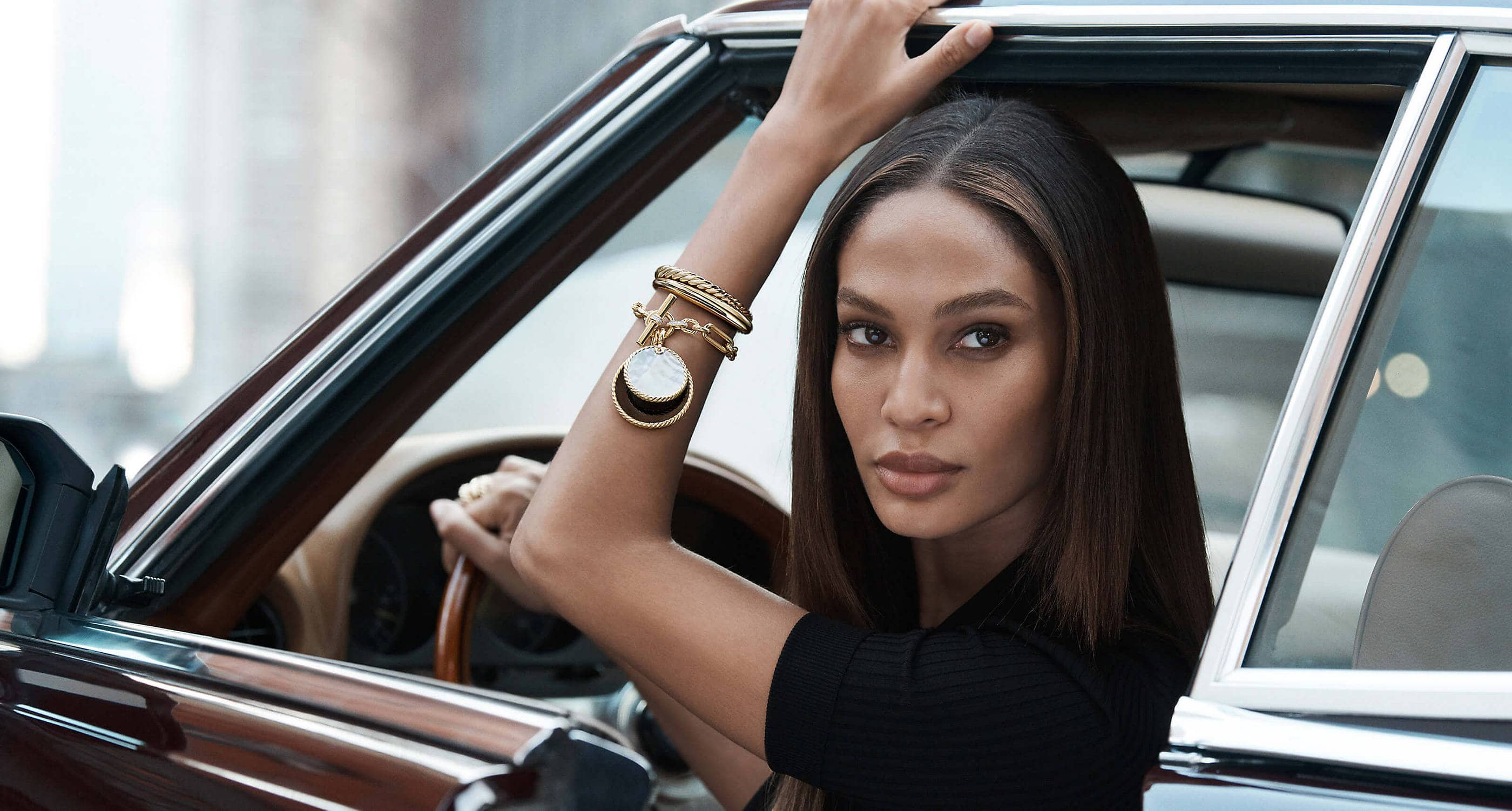 model Joan Smalls from the shoulder up sitting in a car with one arm raised in the window. She's wearing a black top and several David Yurman bracelets with DY Elements enhancers stacked on one wrist. The jewelry is crafted from 18K yellow gold with or without pavé diamonds, mother-of-pearl or black onyx.