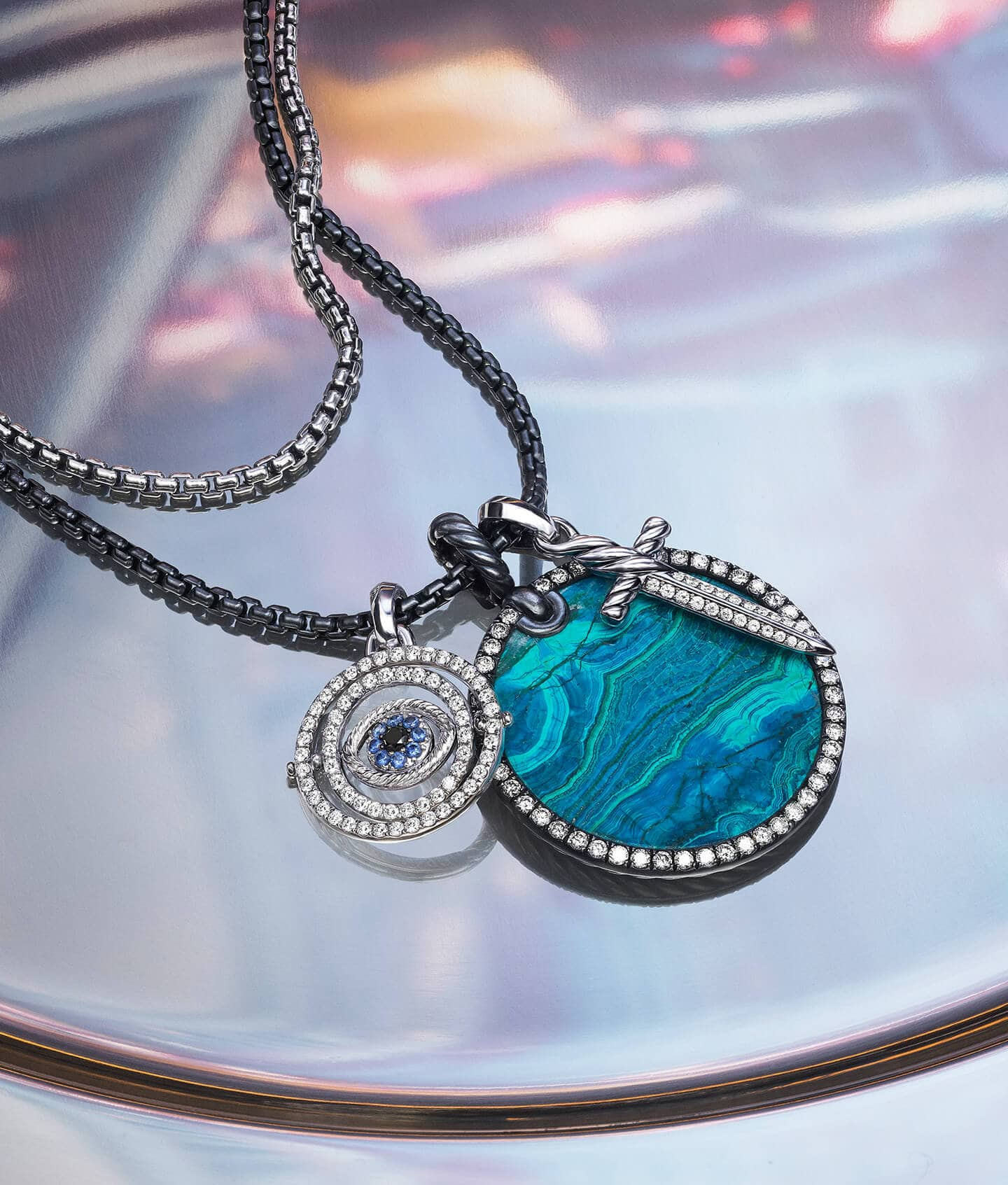 Two David Yurman chains strung with three amulets (also shown right) on a colorful photo of NYC. The center amulet features a circular piece of chrysocolla surrounded by white diamonds. The other two amulets depict an evil eye and a dagger with white diamonds and blue sapphires. The jewelry is crafted from sterling silver, darkened sterling silver or 18K white gold.