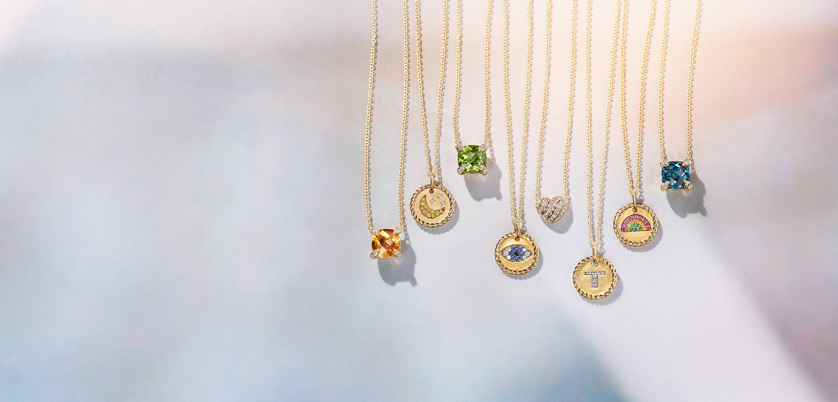 A color photo shows a row of eight David Yurman women's pendant necklaces hanging in front of a white background with colorful reflections. The jewelry is crafted from 18K yellow gold with pavé diamonds. Three of the necklaces feature a cushion-shaped center stone of Madeira citrine, peridot or Hampton blue topaz. The other necklaces depict a moon and stars, an evil eye, the letter T or a rainbow with various colored gemstones. One necklace is shaped like a heart.