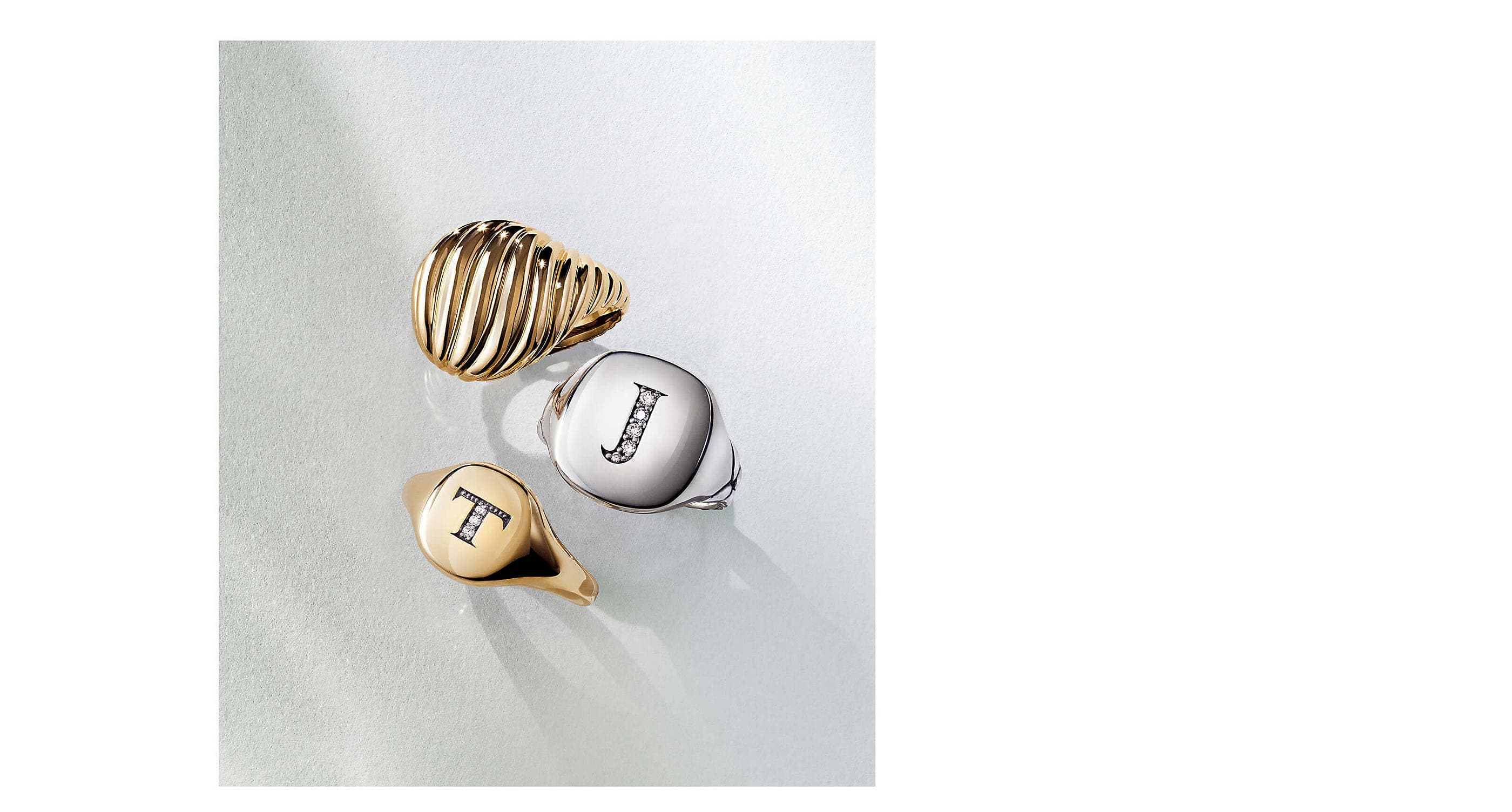 A color photo shows three David Yurman pinky rings on a white background with soft shadows. Two rings are crafted from Cabled or smooth 18K yellow gold with or without a pavé diamond letter T. One ring is crafted from sterling silver with the letter J in pavé diamonds.