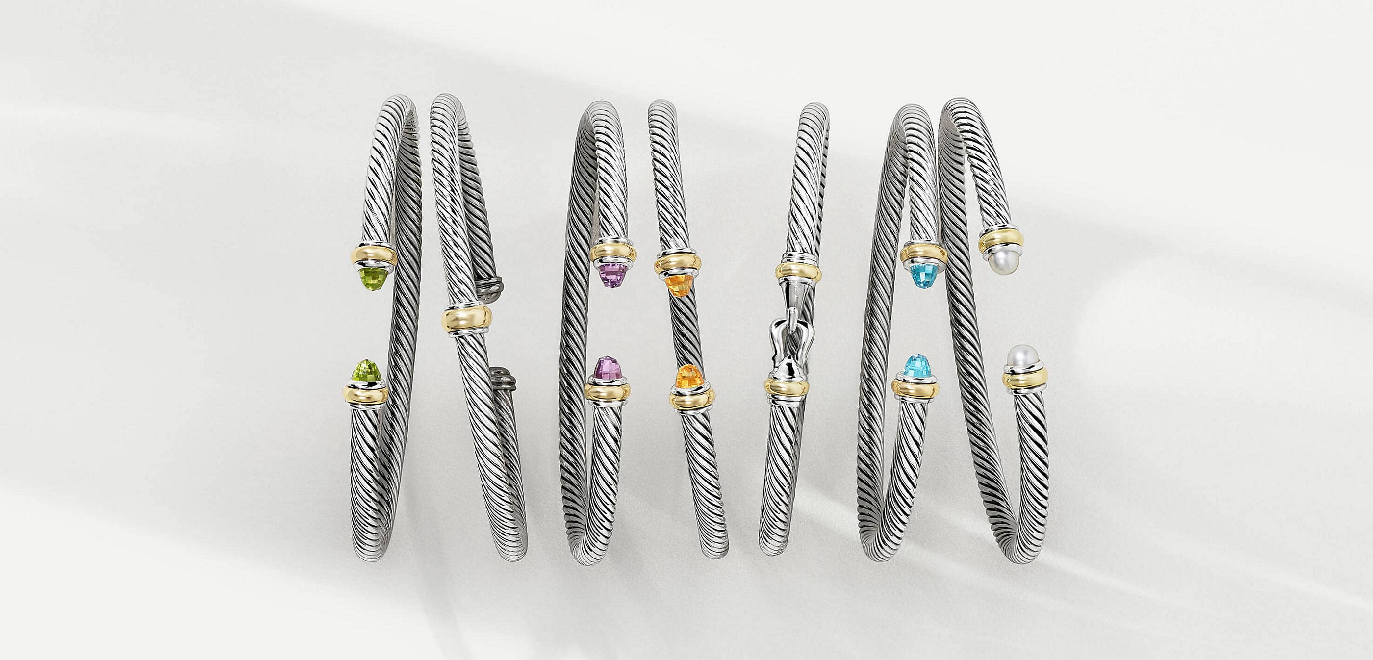 A color photo shows an overhead shot of a horizontal row of seven David Yurman Cable bracelets atop a white background with soft shadows. The jewelry is crafted from sterling silver with 18K yellow gold accents near the end caps. Five bracelets feature gemstones such as cultured pearls, peridot, amethyst, citrine or blue topaz.