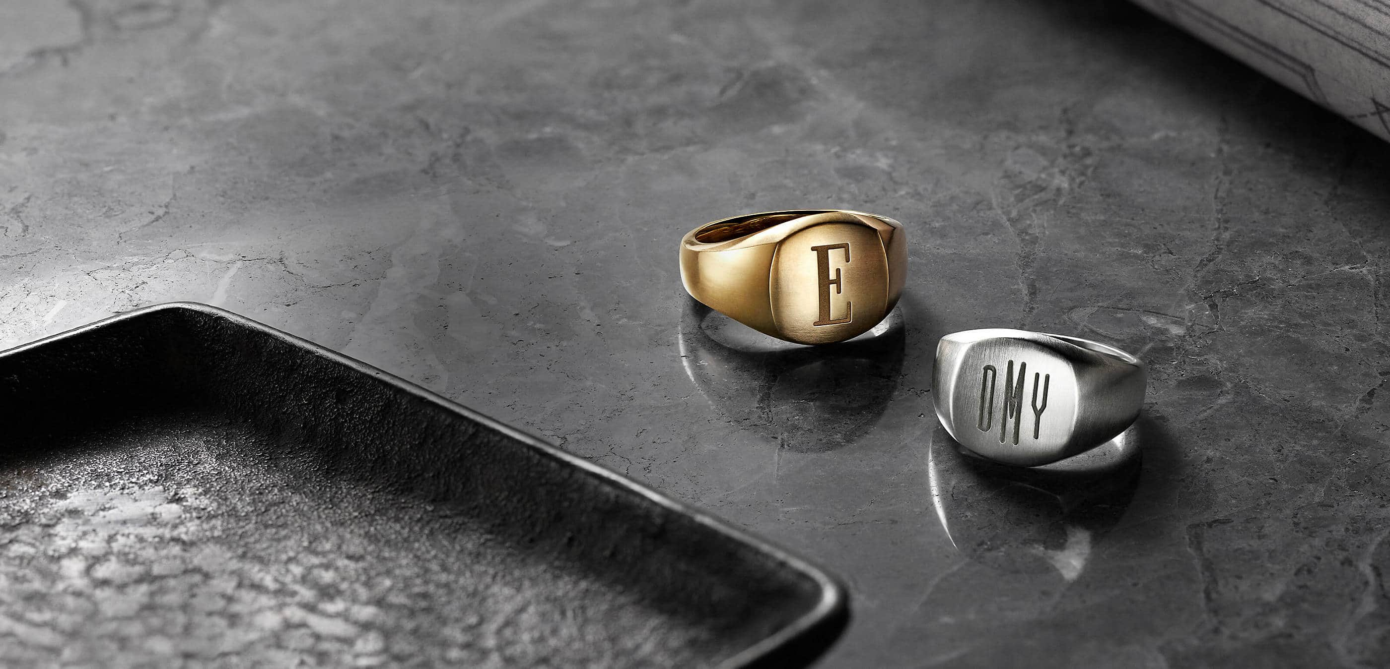 "A color photo shows two David Yurman men's signet rings scattered on a grey marble surface with hard shadows and a dark brown metal tray on the left. One ring is crafted from 18K yellow gold and is engraved with an ""E"". The other ring is crafted from sterling silver and is engraved with the initials ""DMY."""