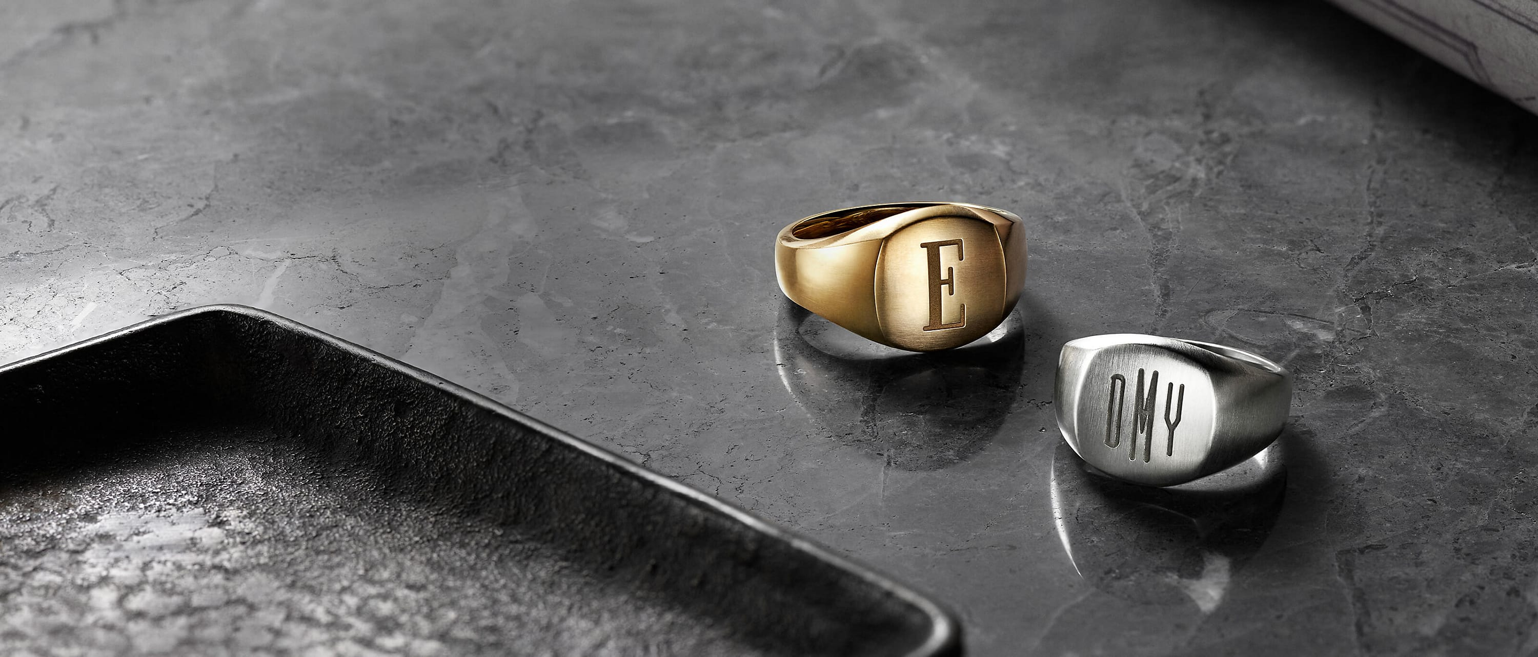 A color photo shows two David Yurman men's signet rings scattered on a dark grey marble surface near a black tray. One ring is crafted from 18K yellow gold and engraved with the letter E. The other ring is crafted from sterling silver and engraved with a DMY monogram.