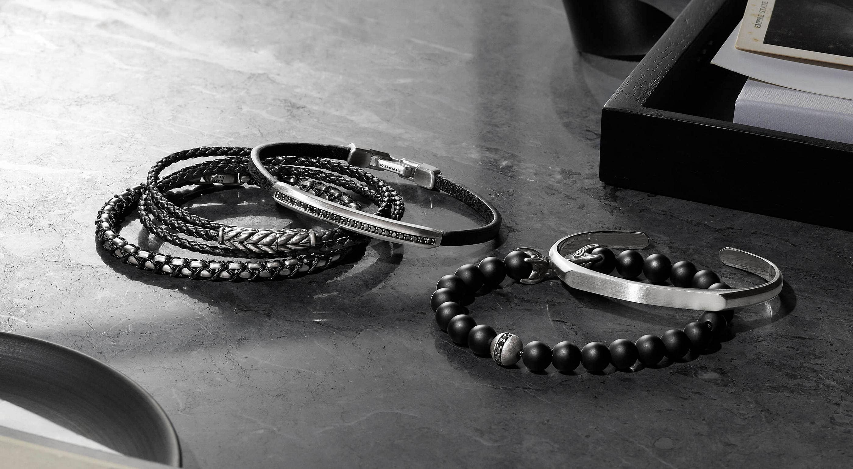 A color photo shows five David Yurman men's bracelets scattered on a grey marble surface in between a black tray and dish holding white papers and black-and-white postcards. The jewelry is crafted from sterling silver. One bracelet is woven with black nylon, two bracelets feature braided black leather and one bracelet is crafted from black onyx beads with black diamond accents.