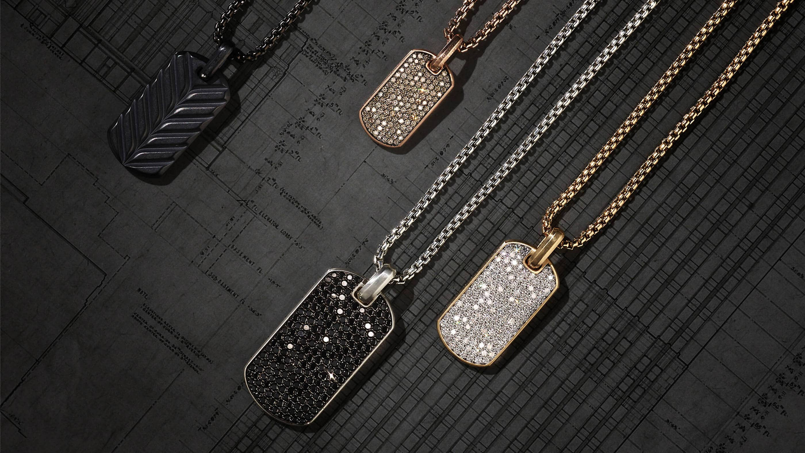 A color photo shows four tags and box chains lying on a dark grey architectural rendering in a diagonal row. The jewelry is crafted of black titanium, blackened stainless steel, 18K rose or yellow gold, or sterling silver with or without cognac, black or white diamonds.