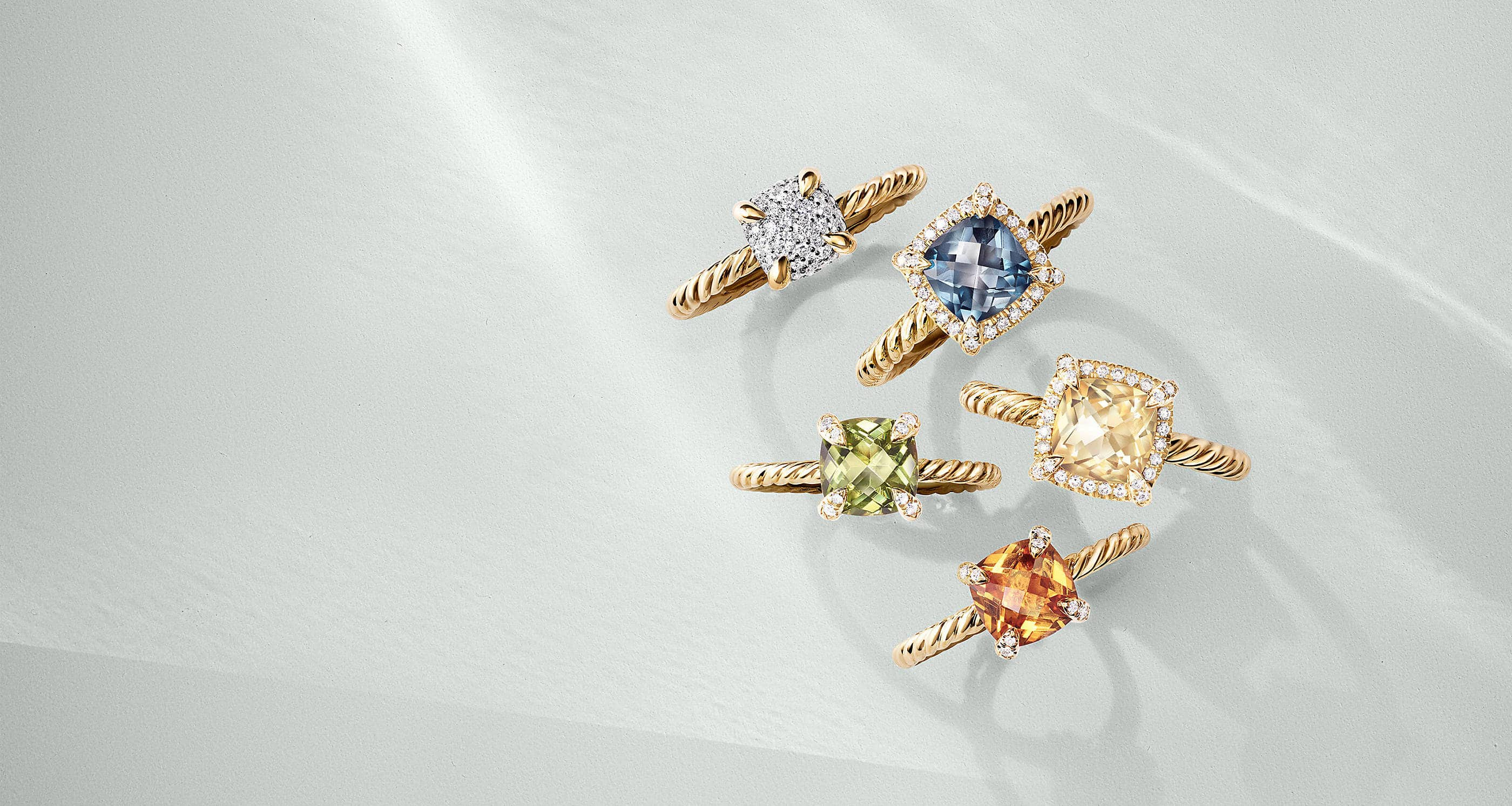 A color photo shows an overhead shot of five David Yurman Châtelaine rings standing on a white background with soft shadows. The jewelry is crafted from 18K yellow gold. One ring features pavé diamonds covering a cushion-shaped center. The other rings feature pavé diamond accents on the bezel or prongs with a center stone of Hampton blue topaz, peridot, Champagne or Madeira citrine.
