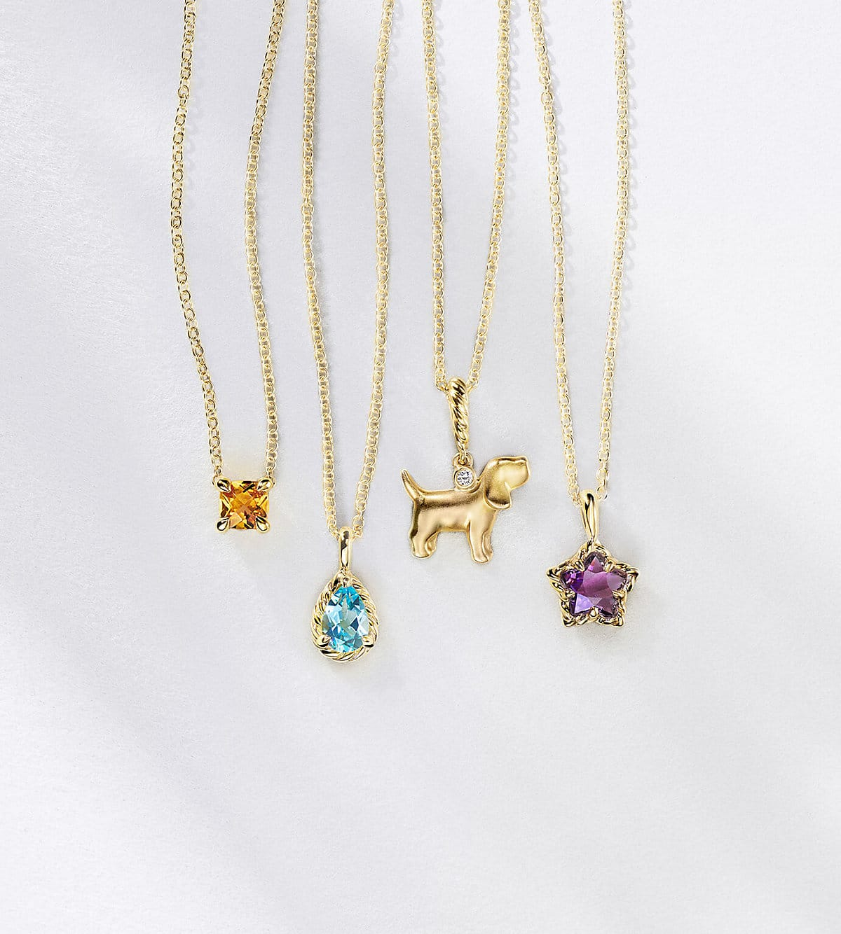A color photograph shows four David Yurman kids' pendant necklaces hanging in a horizontal row in front of a white background with diagonal shadows. The kids' jewelry is crafted from 18K yellow with or without a cushion-cut citrine, teardrop-shaped blue topaz, dog charm with a white diamond and star-shaped amethyst.