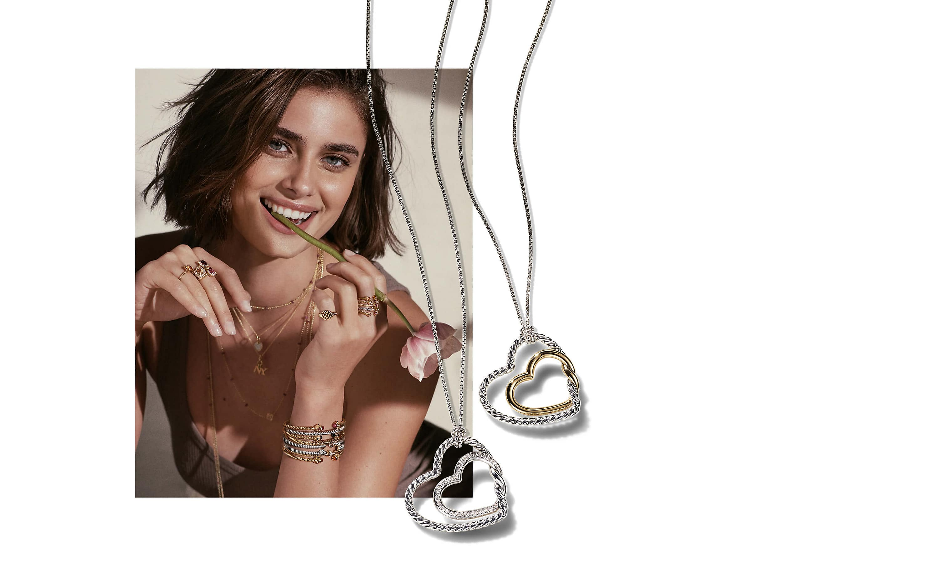 A color photo shows model Taylor Hill from the waist up holding a pink-and-white flower in her hand with the stem in her mouth. She's wearing multiple David Yurman necklaces, rings and bracelets stacked together in 18K yellow gold or sterling silver with various colored gemstones. Juxtaposed on top of the image of Taylor Hill is a color photo showing two David Yurman Continuance heart necklaces. One necklace is crafted from sterling silver with an 18K yellow gold inner heart and the other necklace is crafted from sterling silver with pavé diamond accents on the inner heart.