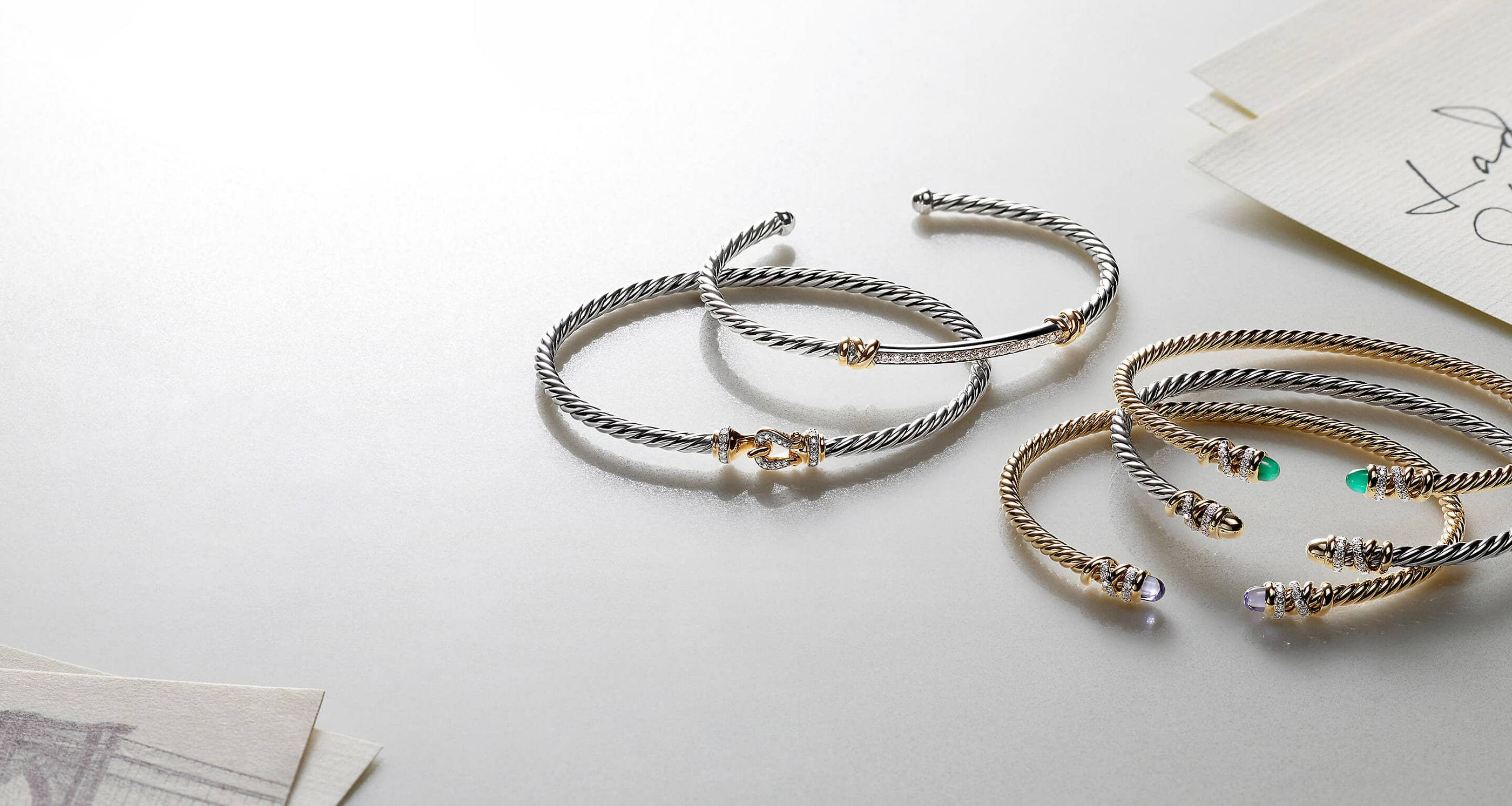 A color photo shows five David Yurman bracelets from the Helena and Buckle collections scattered on a white surface next to a stack of white notecards with black handwriting. Two of the women's bracelets are crafted from 18K yellow gold with pavé white diamond or emerald accents. Three of the women's bracelets are crafted from sterling silver with 18K yellow gold and pavé white diamond accents.