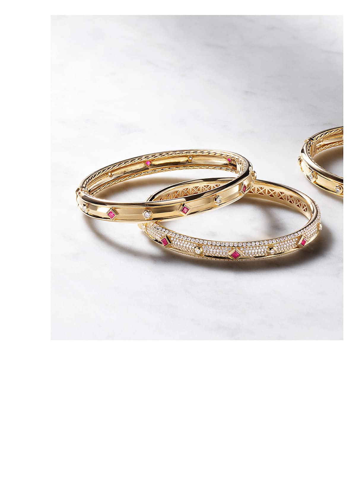 A color photo shows three David Yurman women's bracelets from the Modern Renaissance collection scattered on a grey marble surface. The jewelry is crafted from 18K yellow gold with diamond accents and with or without ruby accents.