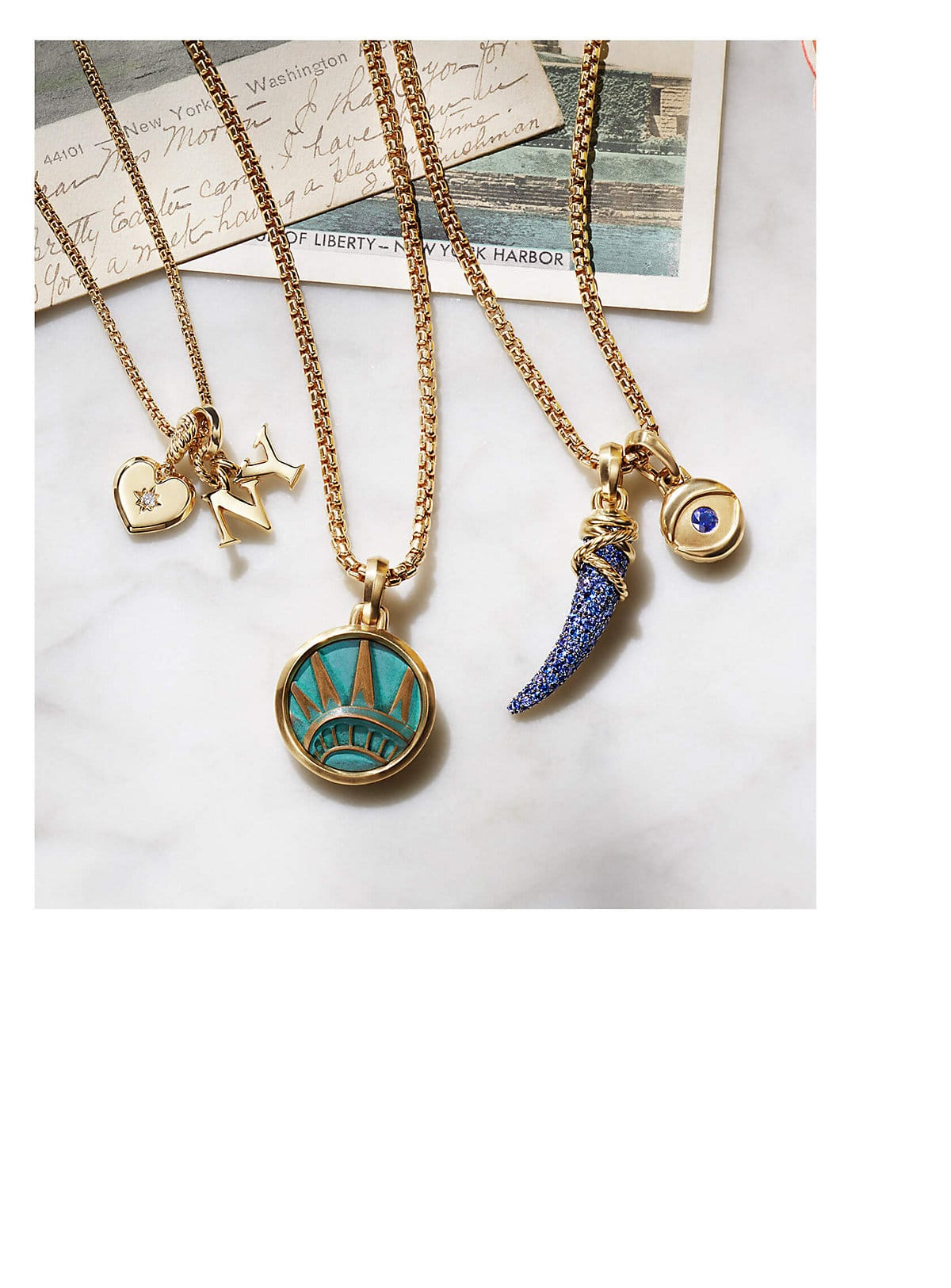 "A color photo shows three David Yurman chain necklaces strung with amulet pendants, all lying on a marble table atop two New York postcards. The women's jewelry is crafted from 18K yellow gold with or without pavé diamonds and sapphires. The pendants come in various shapes such as a heart, dagger, evil eye or ""NY"" initials. One pendant depicts the crown of the Statue of Liberty."