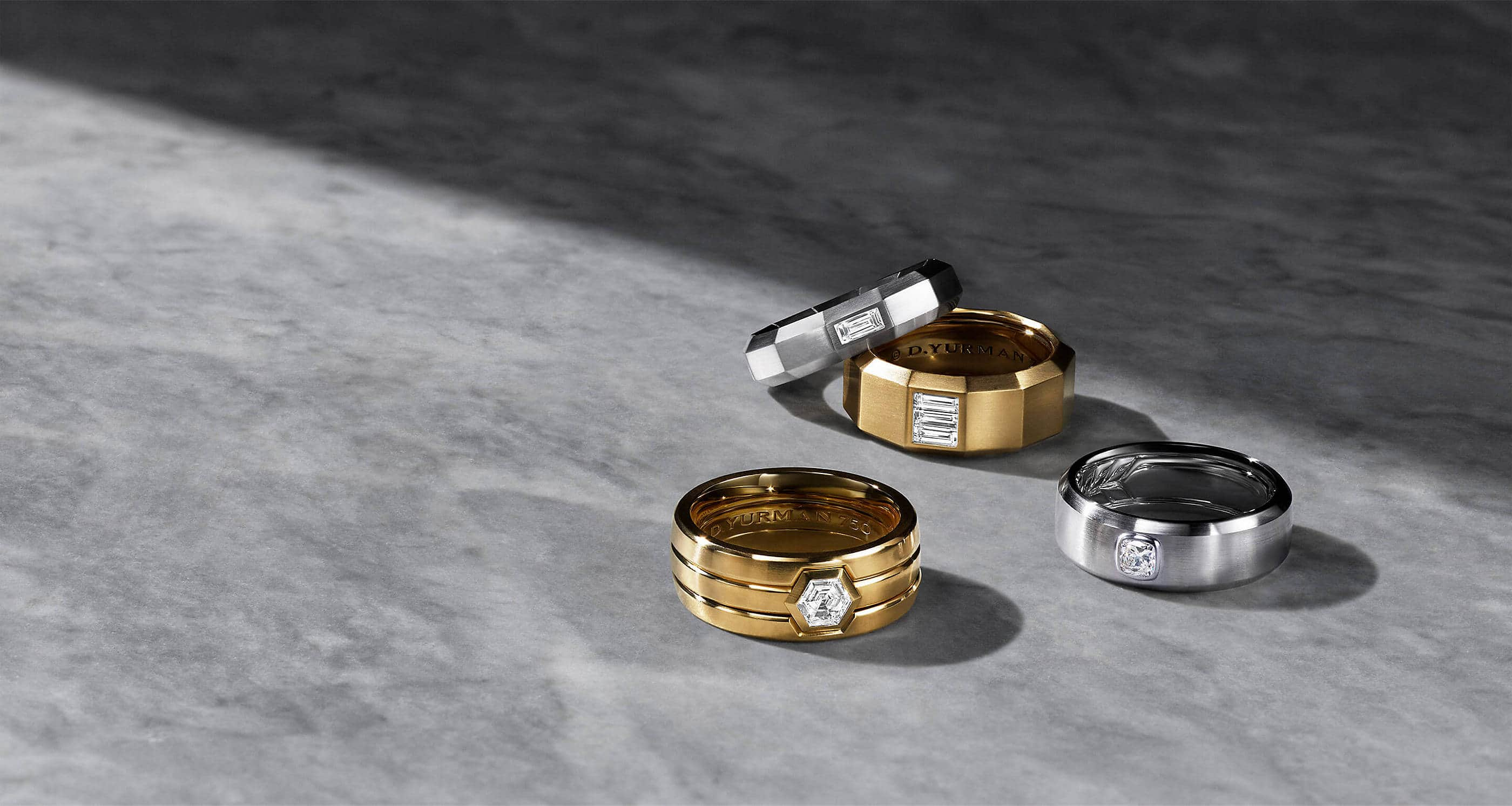 A color photo shows four David Yurman men's band rings scattered on a grey marble surface with hard shadows. The jewelry is crafted from 18K yellow gold or white gold, each with a center diamond.