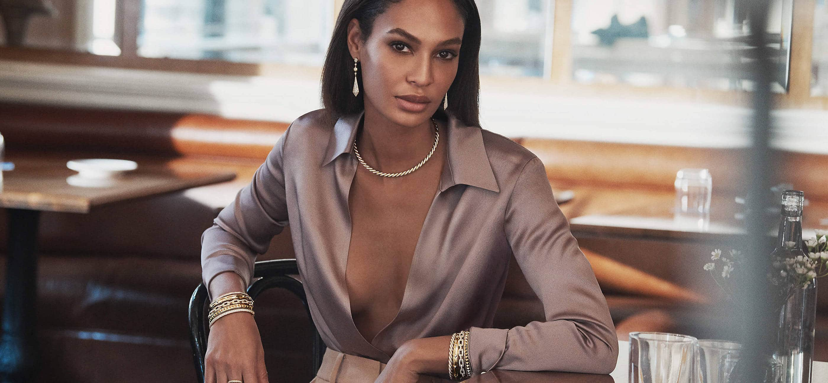 A color photo shows model Joan Smalls from the waist up sitting at a table in a sunlit restaurant near a window and brown leather banquettes. She's wearing a lilac-hued silk blouse that's open in the front and a pair of David Yurman earrings, a necklace and several bracelets stacked on both wrists. The jewelry is crafted from 18K yellow gold with or without pavé diamonds.