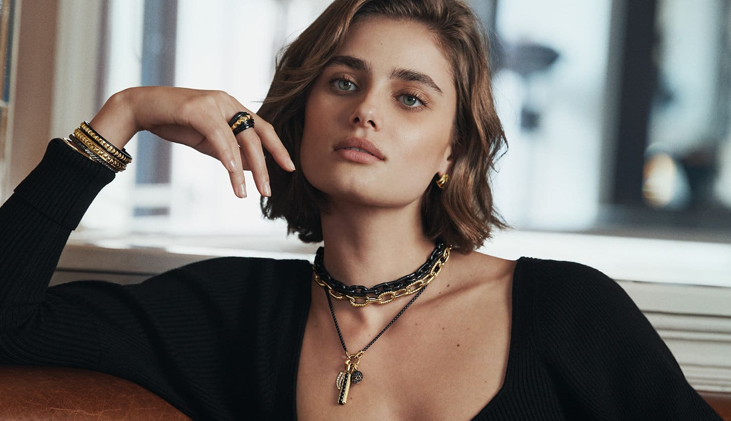 A color photo shows model Taylor Hills from the shoulders up dressed in a black top in front of a sunlit window. She's wearing a paid of David Yurman huggie hoop earrings, a ring, three chain necklaces including one strung with three amulets and a stack of bracelets on one hand. The jewelry is crafted from 18K yellow gold with or without black titanium or white or black diamonds.