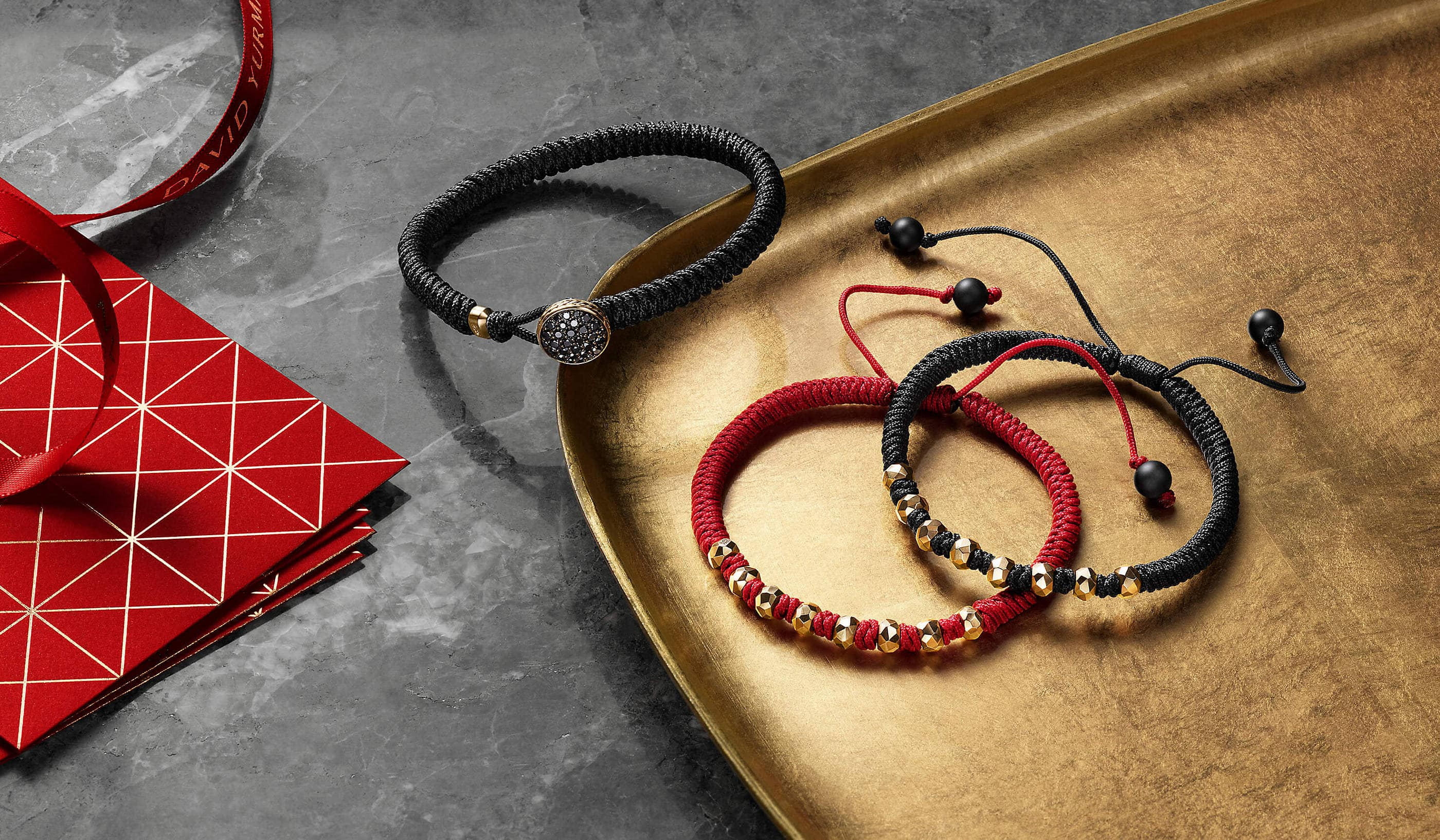 A color photograph shows three David Yurman men's red and black nylon bracelets scattered on a golden tray and a grey marble surface next to a stack of red envelope printed with golden triangles and a red ribbon. The bracelets are crafted from 18K yellow gold. One bracelet has a round clasp covered with black diamonds. Two bracelets have black onyx beads.