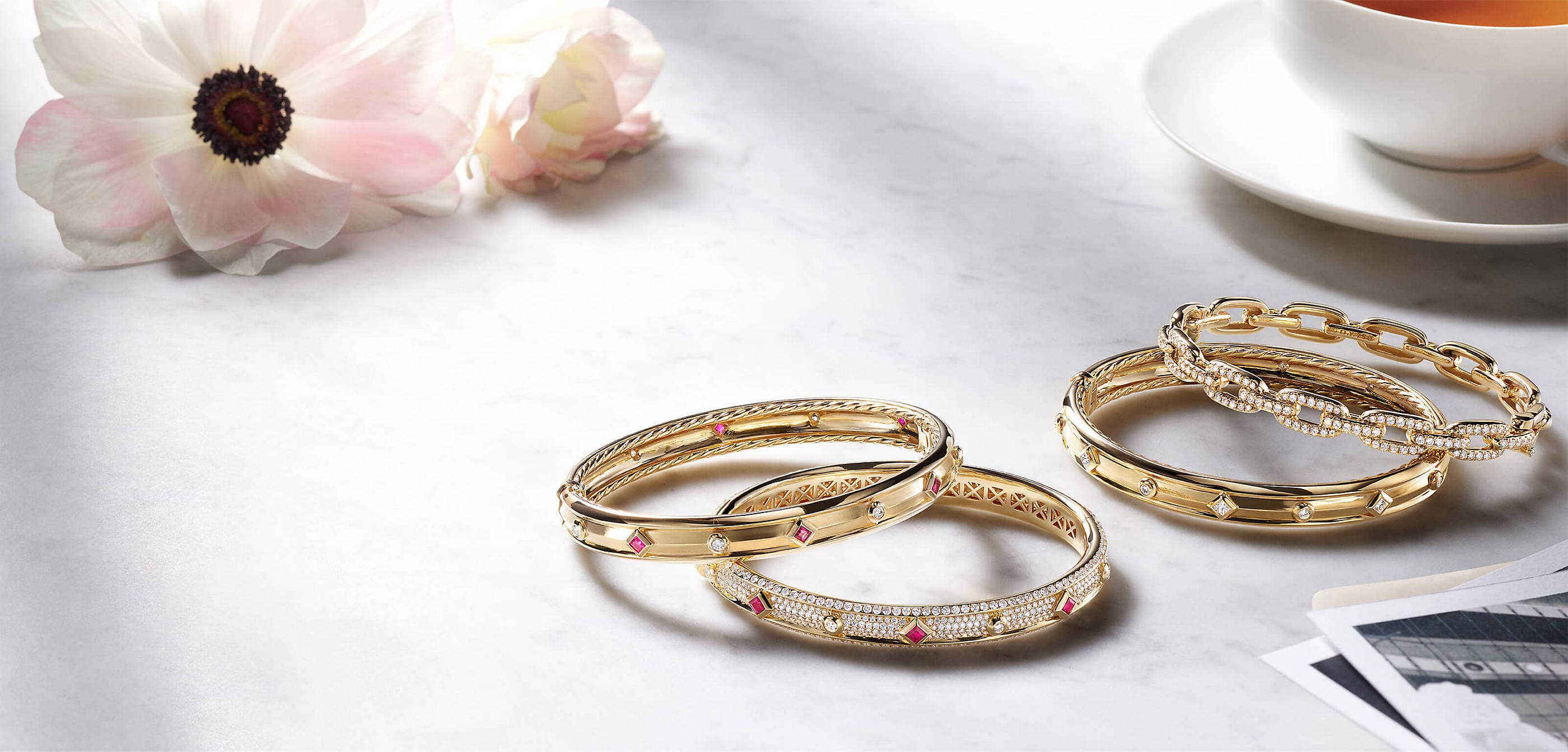 A color photo shows four David Yurman women's bracelets from the Modern Renaissance and Stax collections scattered on a grey marble surface nearby a white cup and saucer, black-and-white photos and a pink-and-white flower. The jewelry is crafted from 18K yellow gold with diamond accents and with or without ruby accents.