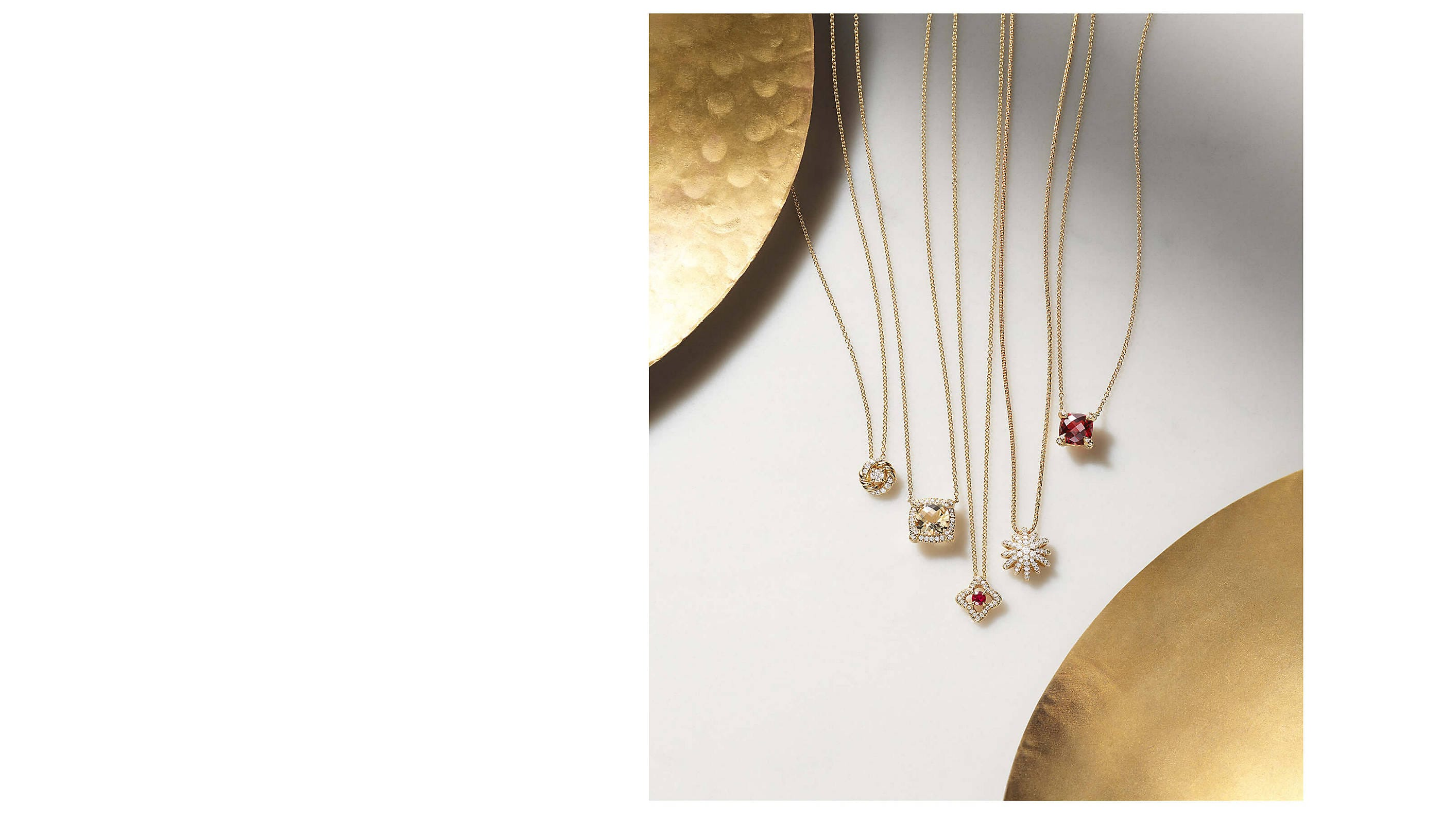 A color photograph shows a row of David Yurman women's pendant necklaces on a white surface in between two golden dishes. The necklaces are crafted from 18K yellow gold with pavé diamonds. Two necklaces have garnet center stones and one necklace has a Champagne citrine center stone.