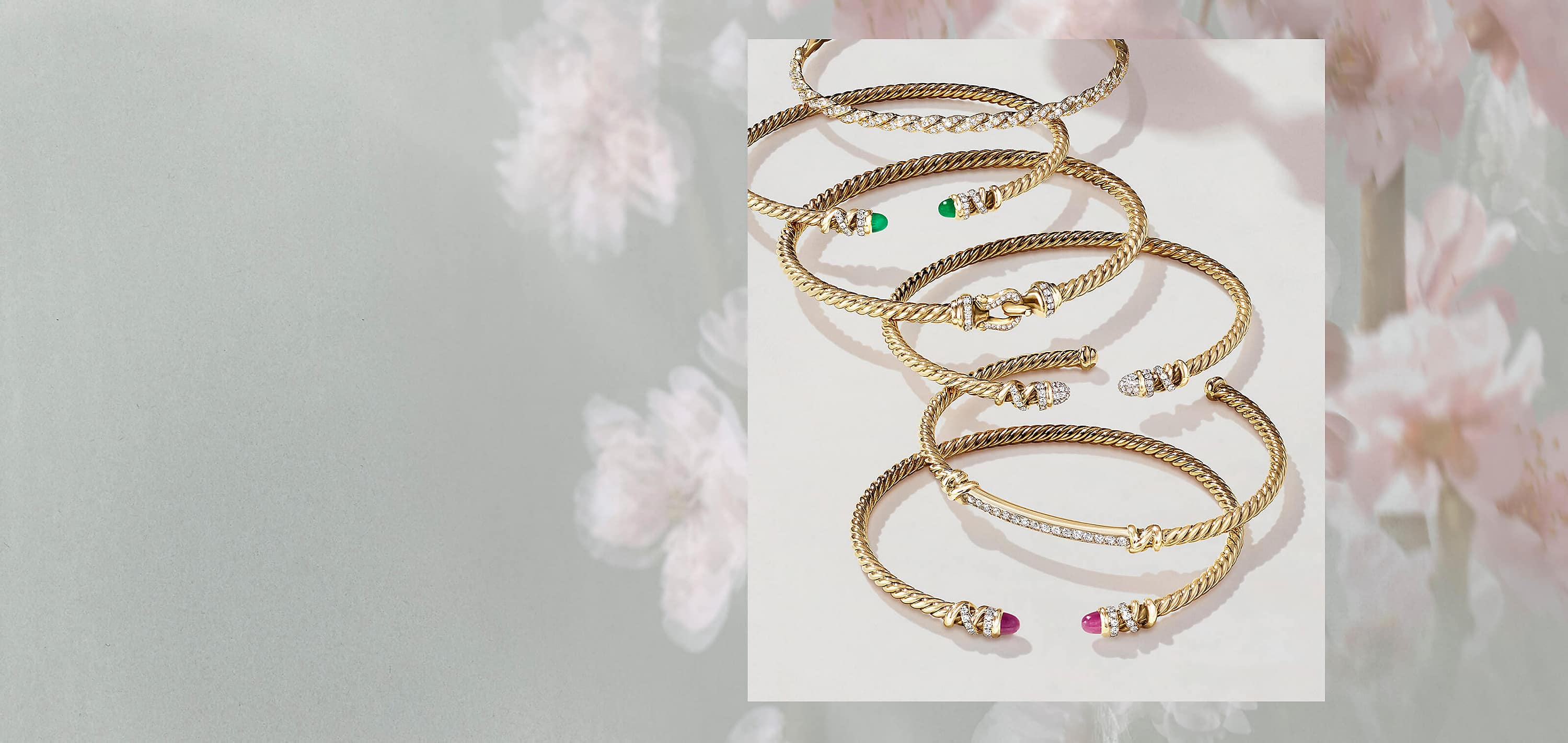 A photo collage places a color photo of six David Yurman Cable bracelets inside a border of soft-focus magnolia flowers. The center image shows the bracelets scattered on a white background. The jewelry is crafted from 18K yellow gold with pavé diamonds and with or without emeralds or rubies.