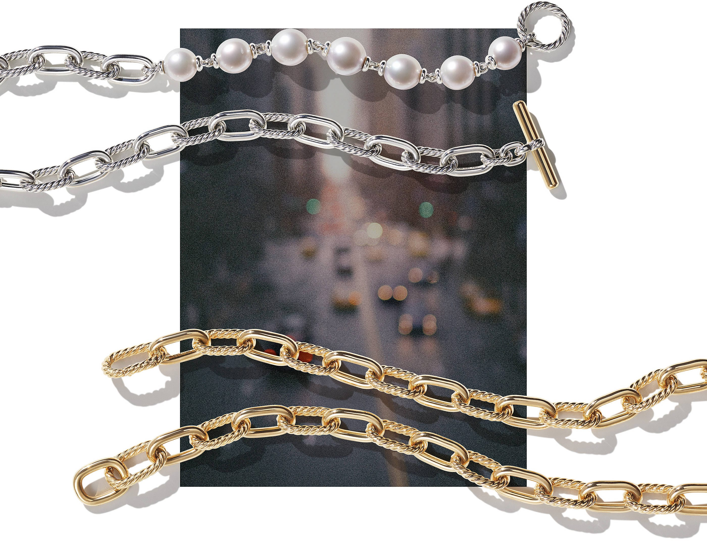 A color photograph shows two David Yurman DY Madison chain necklaces lying atop a soft-focus image of a street in NYC with cars and buildings. The top necklace is crafted from sterling silver with cultured South Sea pearls and an 18K yellow gold toggle. The bottom necklace is crafted from 18K yellow gold.
