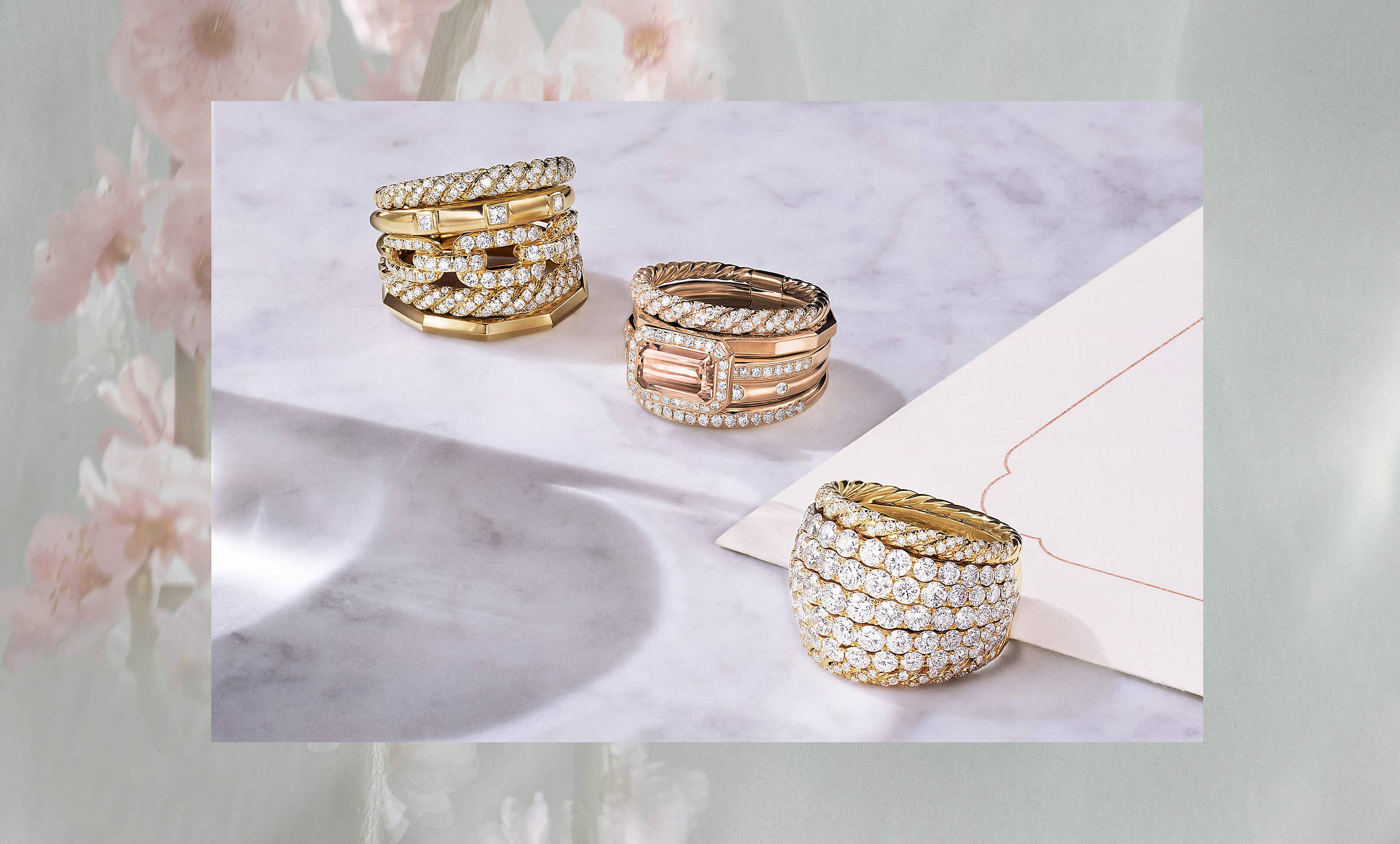 A color photo of three David Yurman multi-row rings is placed inside a border of soft-focus magnolia flowers. The center photo shows the rings scattered on a grey marble surface in between a glass of water and a white notecard. Two of the rings are crafted from 18K yellow gold with pavé diamonds. The center ring is crafted from 18K rose gold with a morganite center stone and pavé white diamonds.