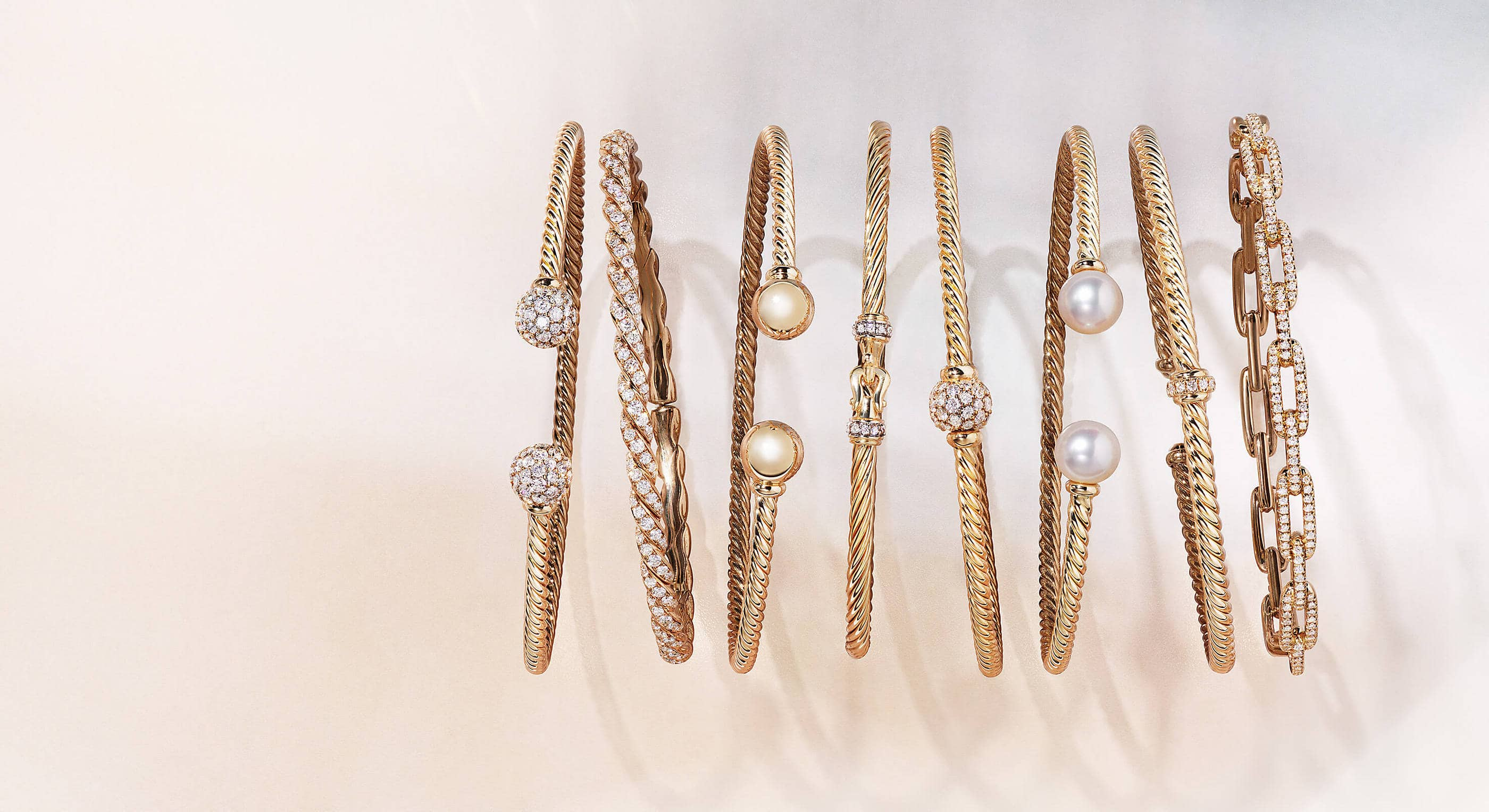 A color photo shows a horizontal row of eight David Yurman Cable and chain-link bracelets atop a light pink-hued stone with soft shadows. The jewelry is crafted from 18K yellow gold with or without pavé diamonds or cultured pearls.