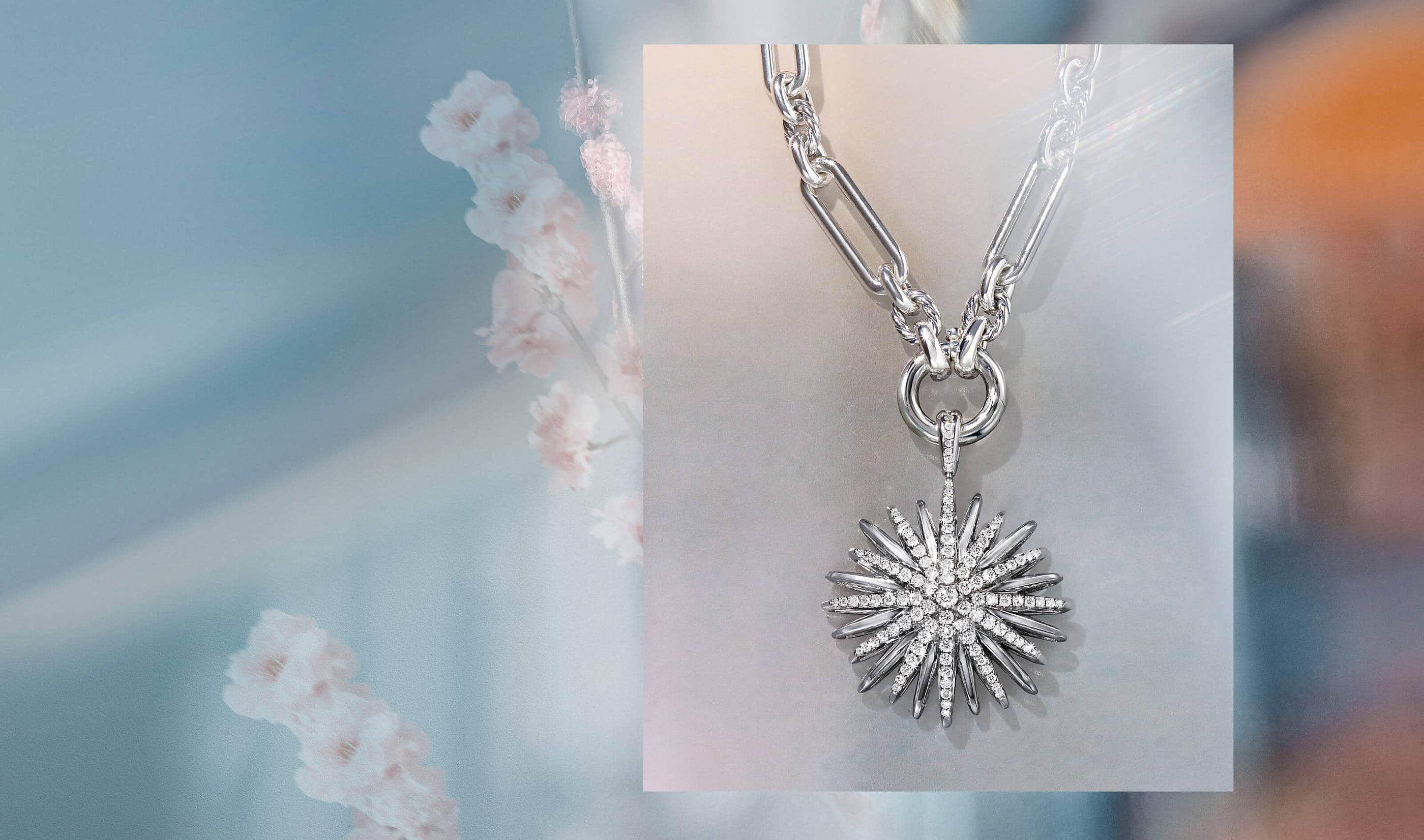A color photo shows a close-up shot of a David Yurman Lexington chain with a Starburst pavé diamond enhancer hanging in front of an opalescent background. The jewelry is crafted from sterling silver.