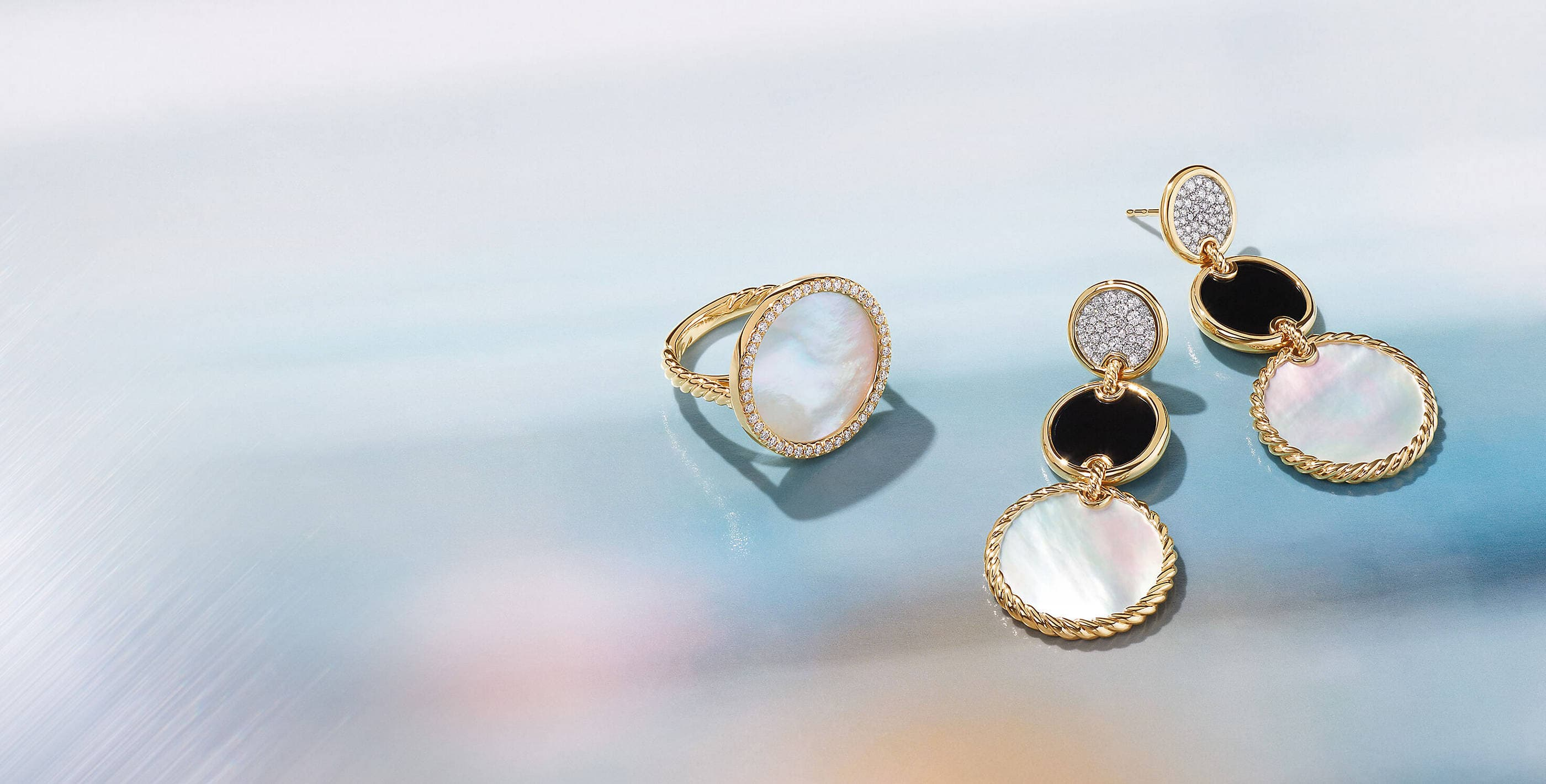 A color photo shows a David Yurman Elements ring placed next to a pair of Elements drop earrings on an opalescent background. The jewelry is crafted from 18K yellow gold with pavé diamonds, mother-of-pearl and black onyx.