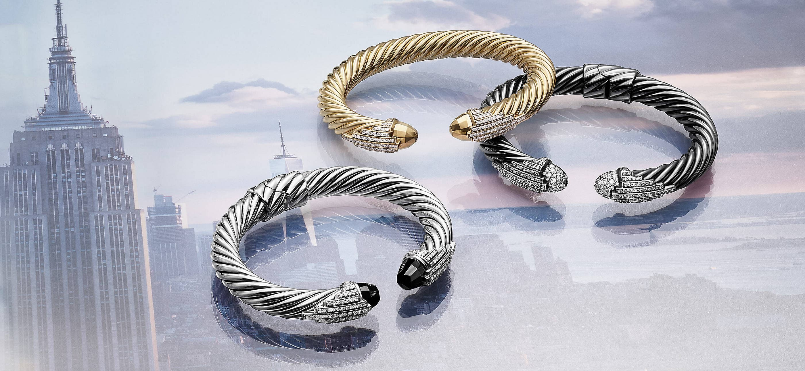 A photo collage layers a color photo of three David Yurman Empire Collection Cable bracelets over a soft-focus photo of the top of the Empire State Building. The jewelry is crafted from sterling silver with or without 18K yellow gold, black onyx or pavé diamond end caps.