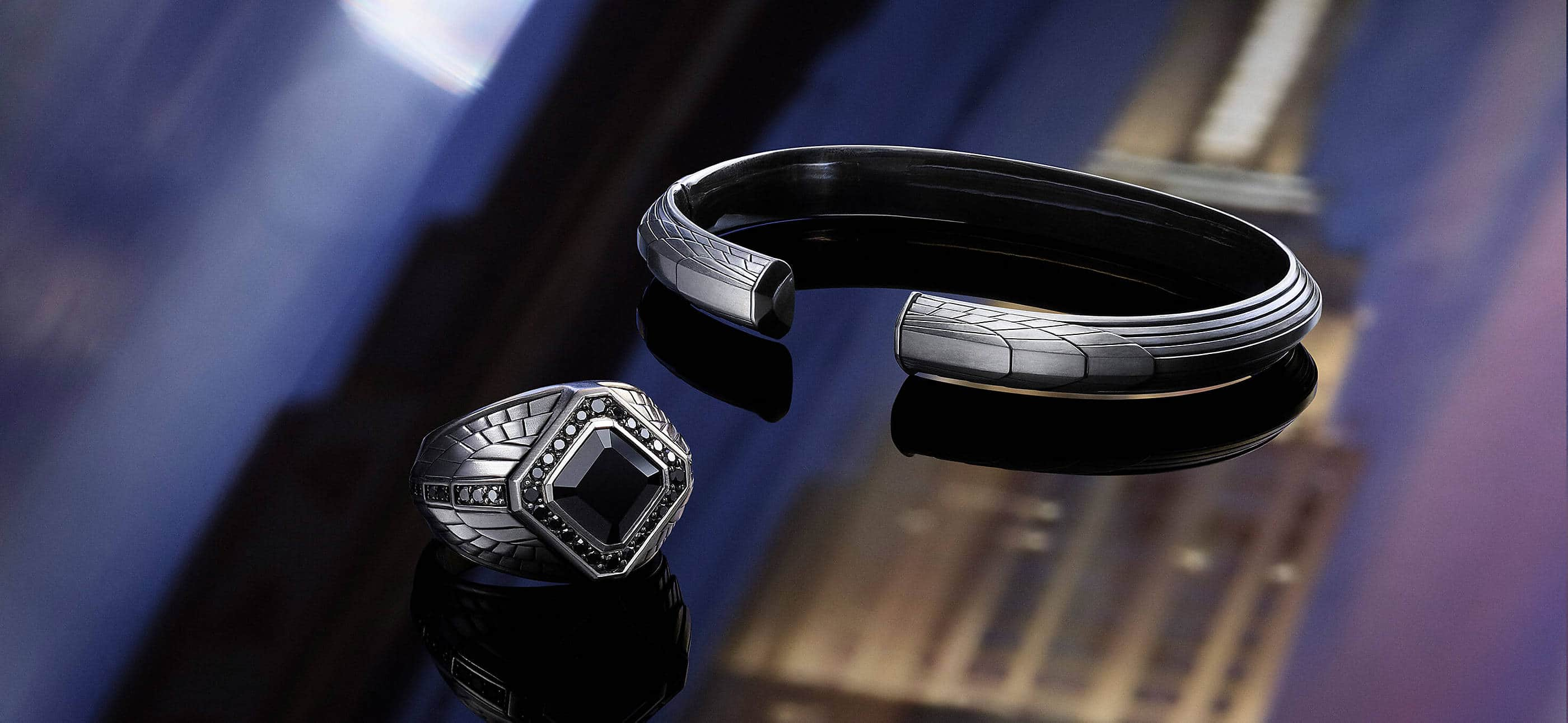 A color photo shows a David Yurman men's signet ring and cuff from the Empire Collection atop a dark surface with reflections of the Empire State Building. The jewelry is crafted from sterling silver with or without black onyx.