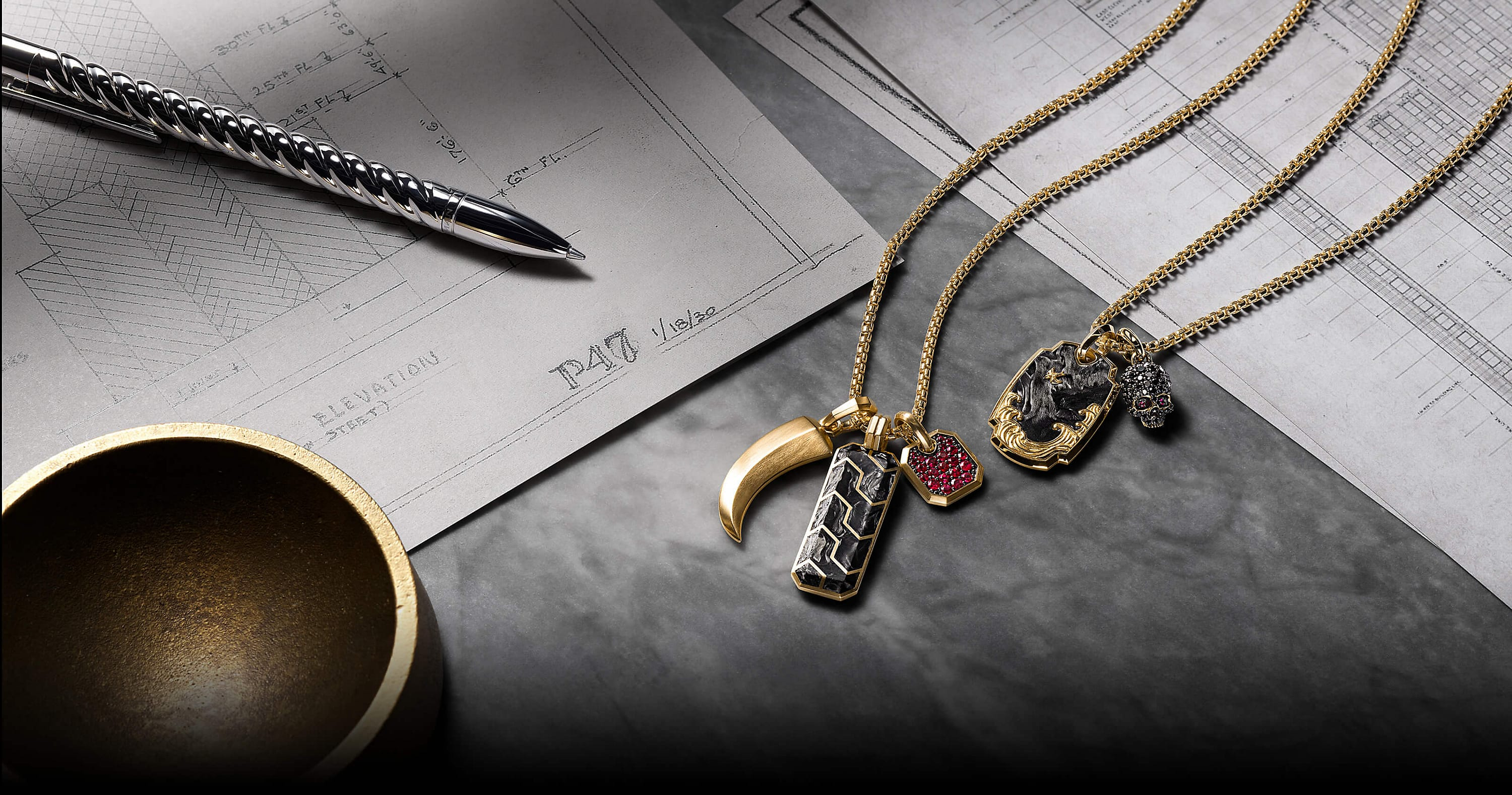 A color photo shows two David Yurman men's chains strung with three or two amulet pendants each. The jewelry is crafted from 18K yellow gold with or without forged carbon, rubies or black diamonds. The amulets come in various shapes such as a dog tag, horn, octagon or skull. The jewelry is placed on a grey marble surface with architectural blueprints, a sterling silver David Yurman Cable pen and a golden dish.