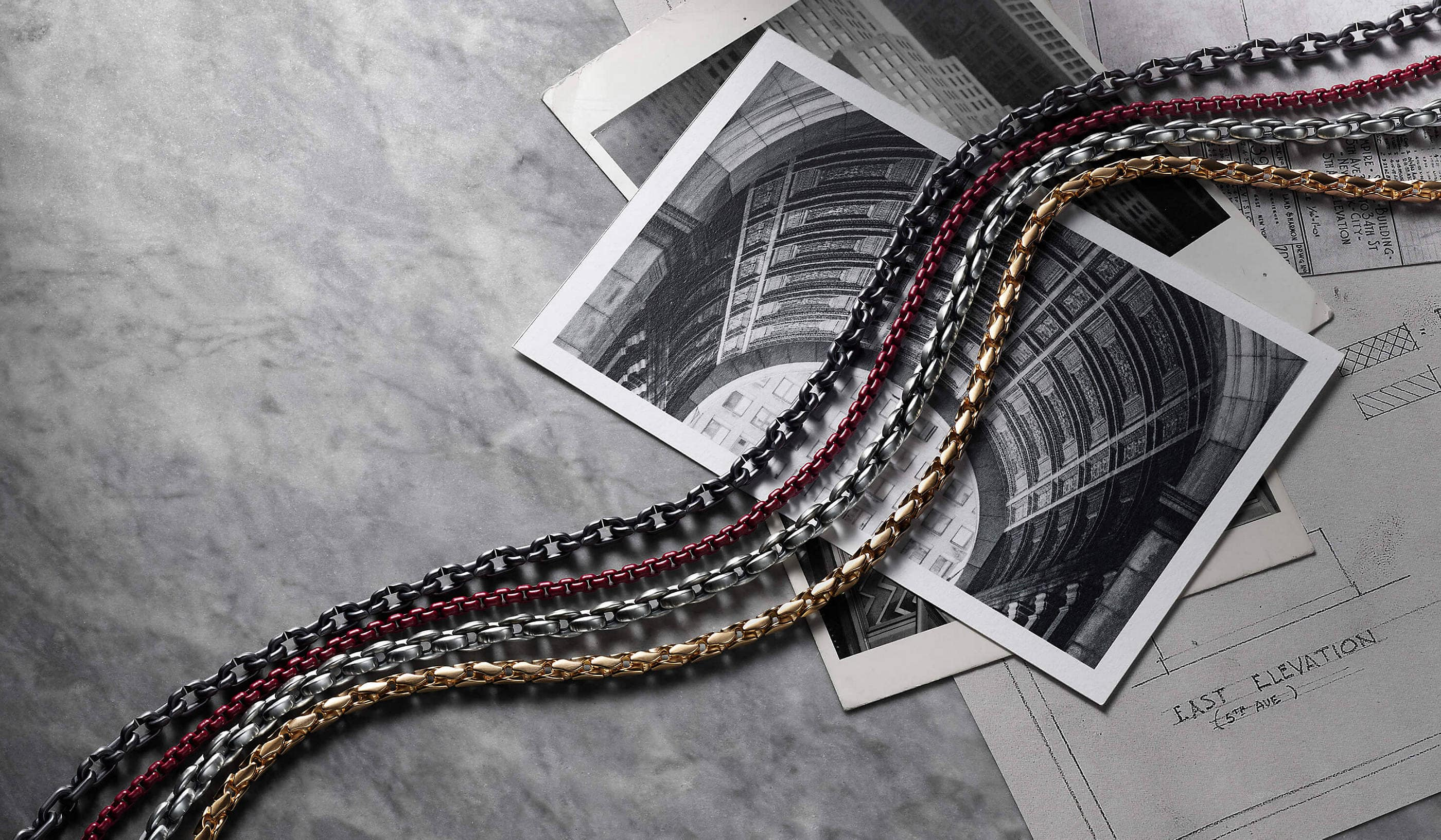 A color photograph shows four David Yurman men's box-chain necklaces arranged in a row atop black-and-white architectural photographs scattered on a grey marble surface. One necklace is crafted from sterling silver, one necklace is crafted from 18K yellow gold, one necklace is crafted from red-hued stainless steel and the last necklace is crafted from grey titanium.