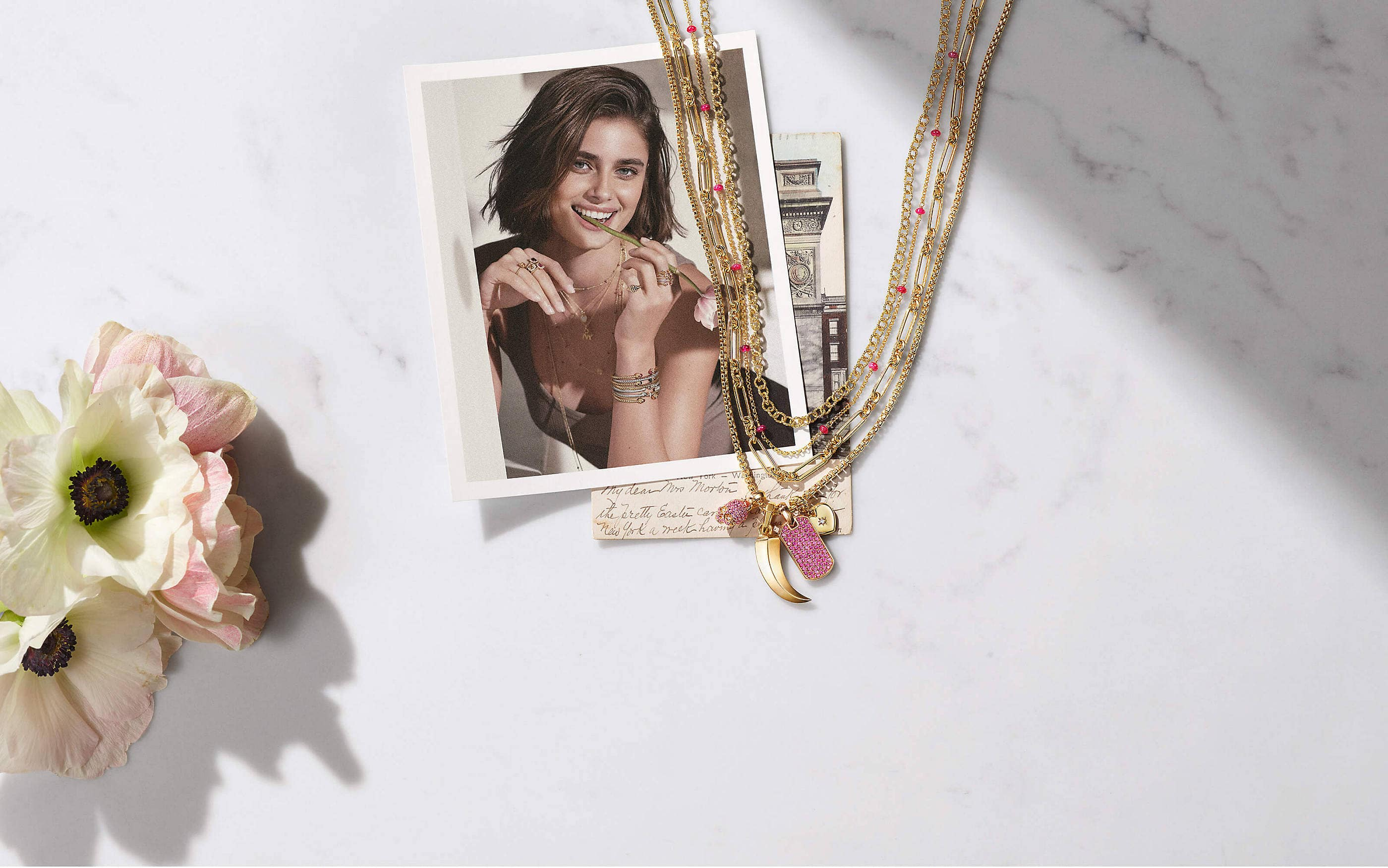 A color photo shows four David Yurman chain necklaces strung with three amulet pendants, all lying on a color photograph and a postcard on a marble table next to a pink-and-white flower. The women's jewelry is crafted from 18K yellow gold with or without pink sapphires. The pendants come in various shapes such as a skull, a dagger and a dog tag. The photograph on the table shows model Taylor Hill holding a pink-and-white flower in her hand with the stem in her mouth. She's angled behind a white wall and wearing multiple David Yurman necklaces, rings and bracelets stacked together in 18K yellow gold or sterling silver with various colored gemstones.
