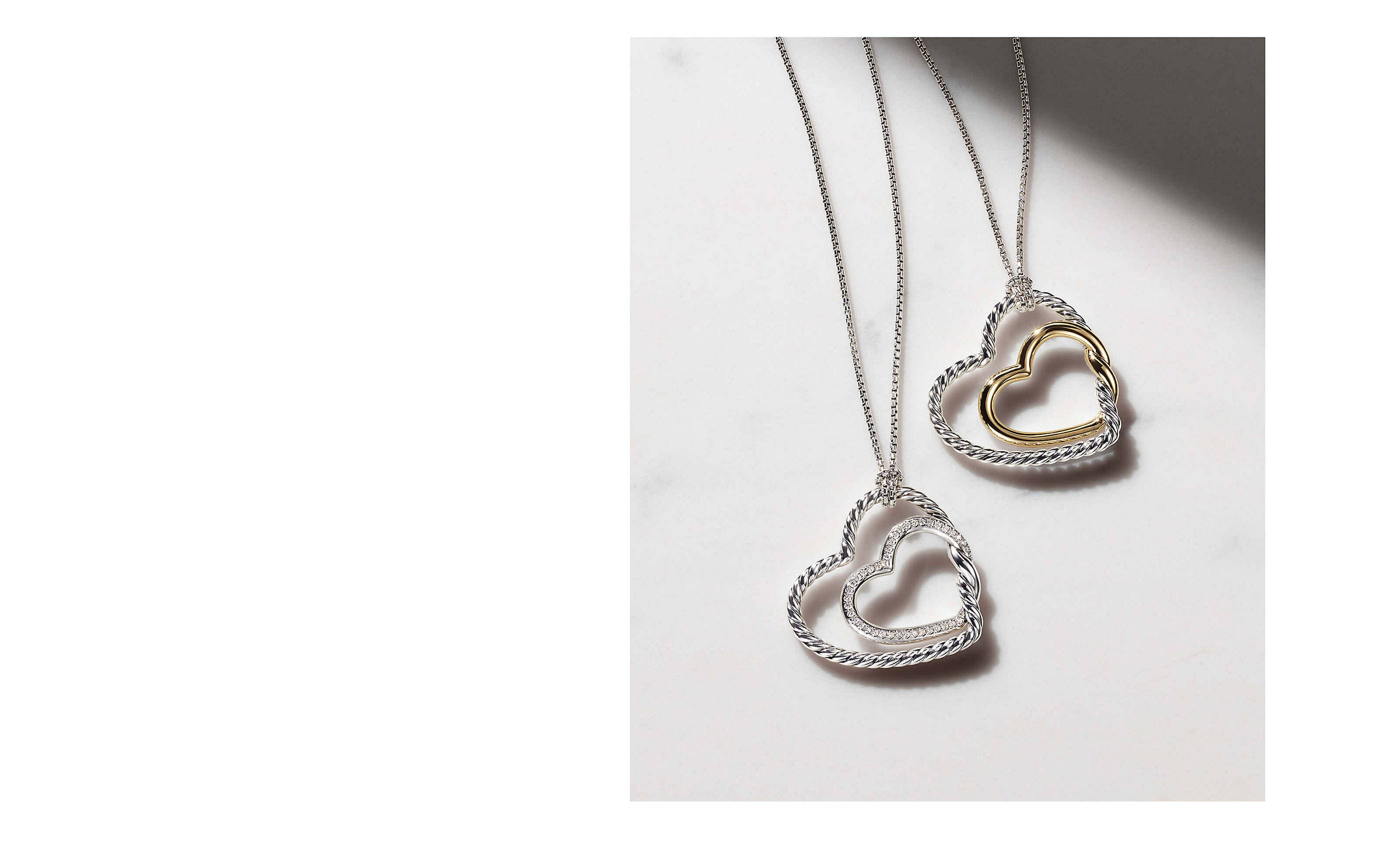 A color photo shows two David Yurman Continuance heart necklaces lying on a marble table atop the New York Times and nearby a white saucer. The women's jewelry is crafted from 18K yellow gold with pavé diamond accents near its tasseled ends.