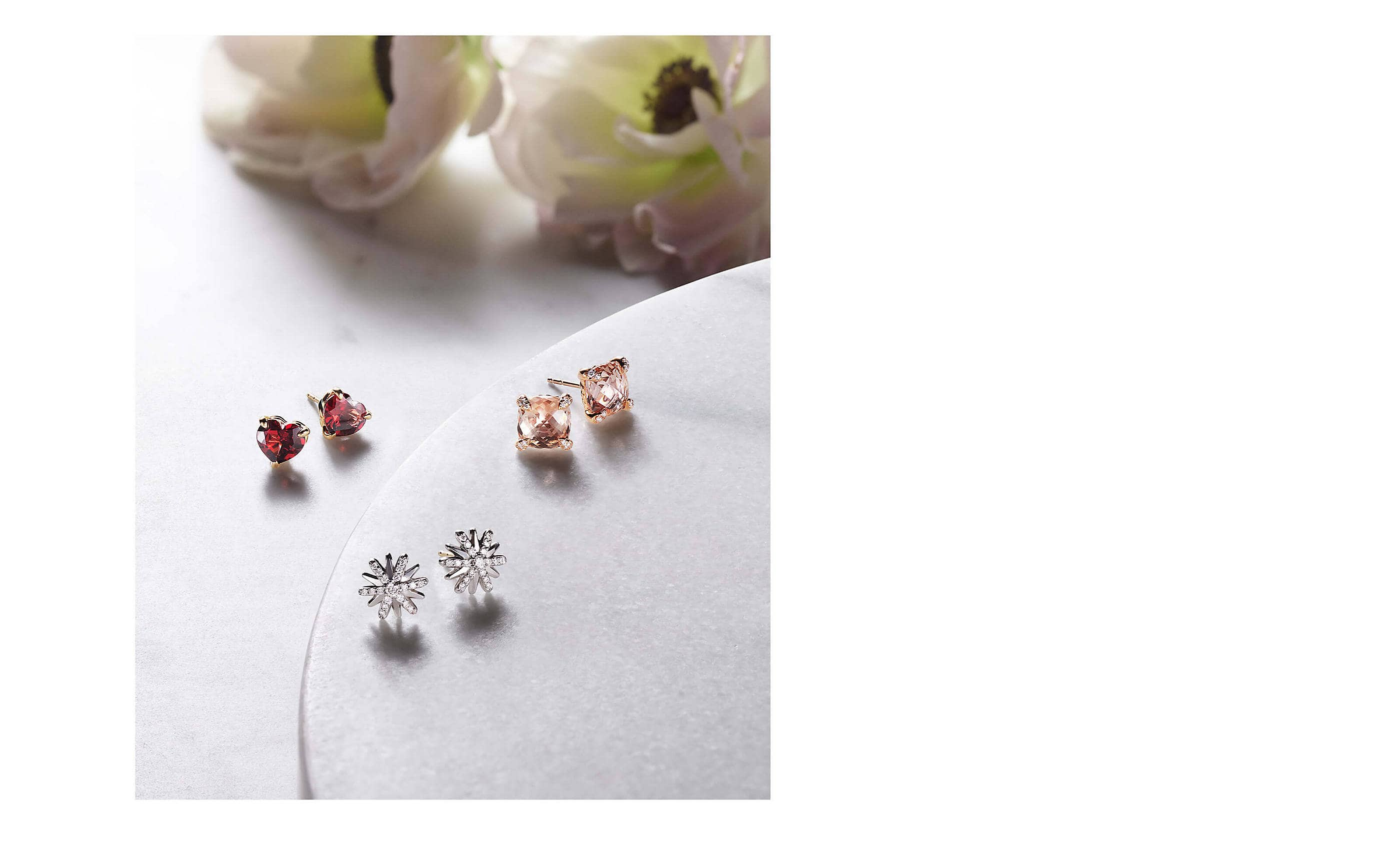 A color photo shows three pairs of David Yurman women's stud earrings scattered on a grey marble surface nearby two white-and-pink flowers. One pair is crafted from 18K yellow gold with heart-shaped garnet, one pair is star shaped and crafted from 18K white gold with pavé diamonds. The last pair is crafted from 18K yellow gold with cushion-shaped morganite.